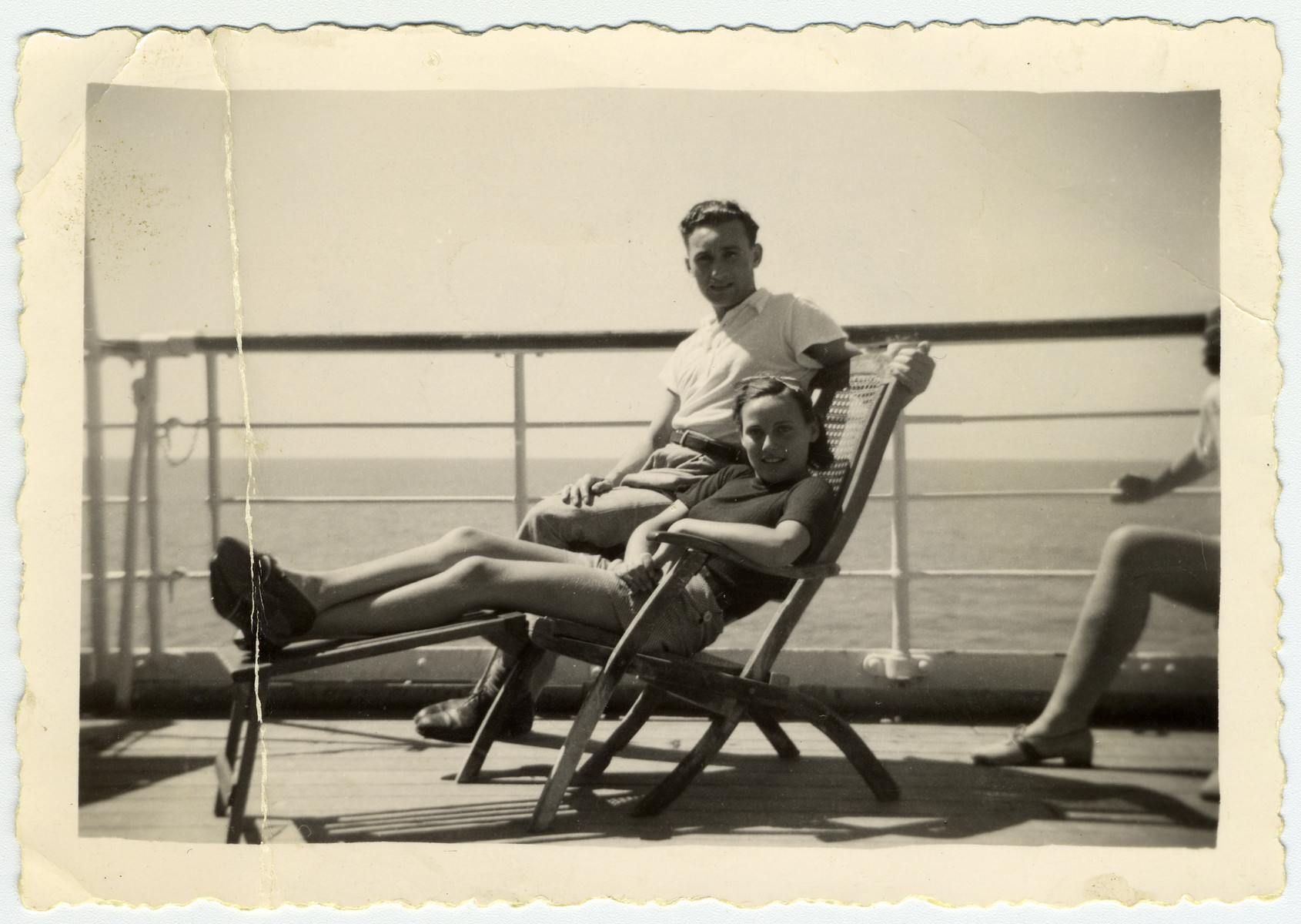 A young couple relaxes on a deck chair during their voyage to Africa where they are being deported as enemy aliens.
