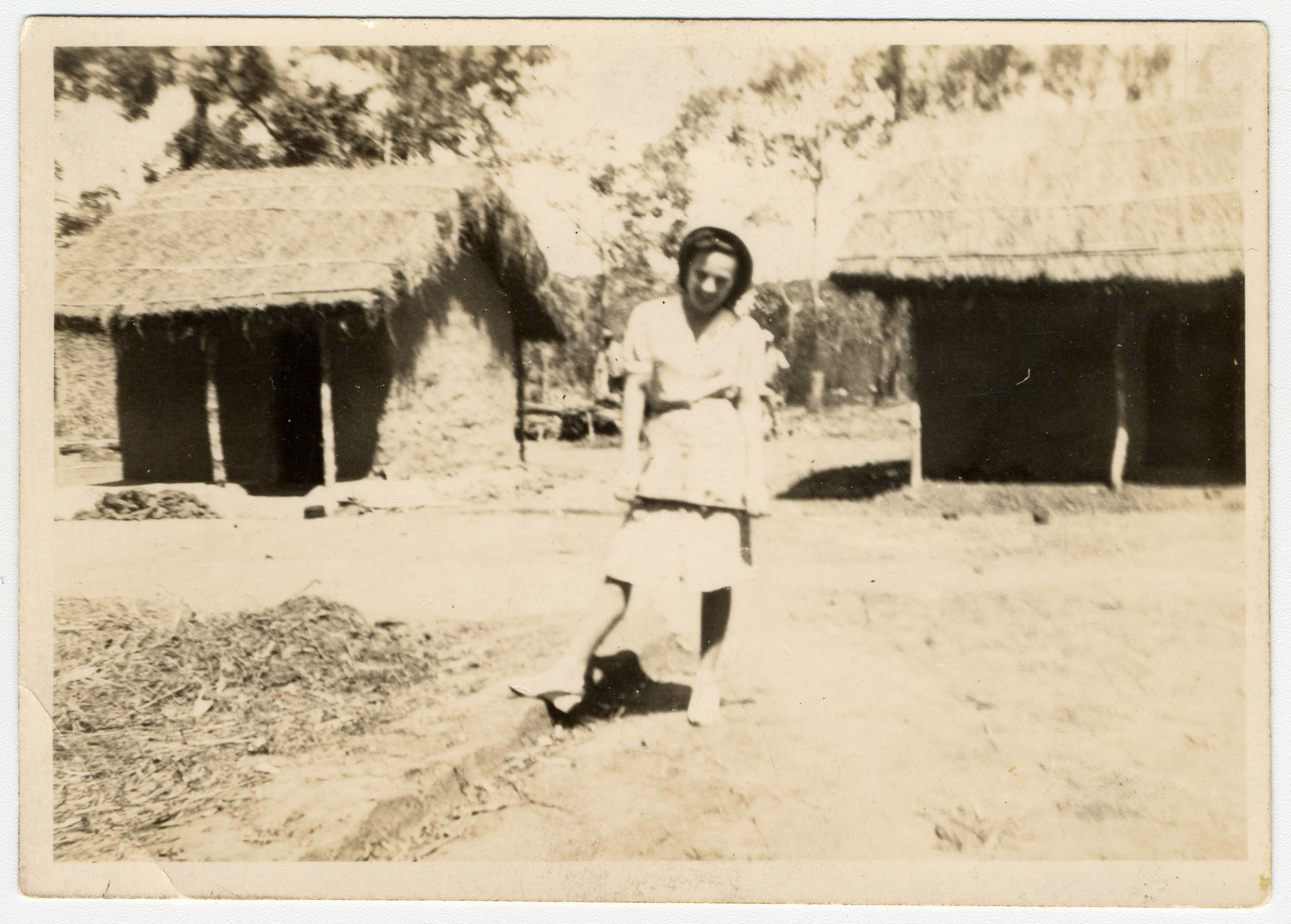 A female internee poses between two grass thatched huts in an interment camp for enemy aliens in Nyasaland.  Pictured is Lily Haber.