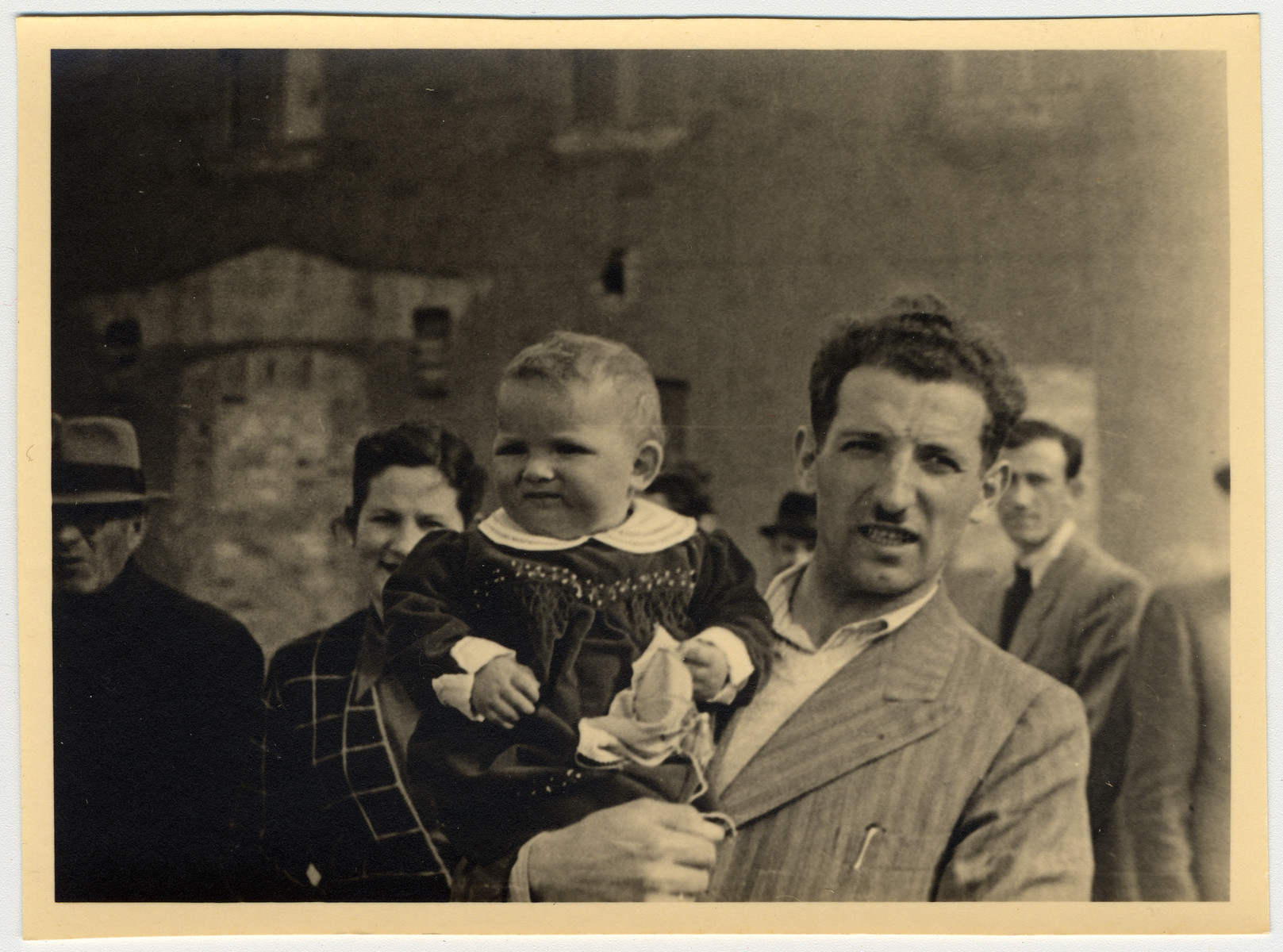 A Jewish displaced person holds his young child in [what probably is the Landsberg displaced persons' camp].