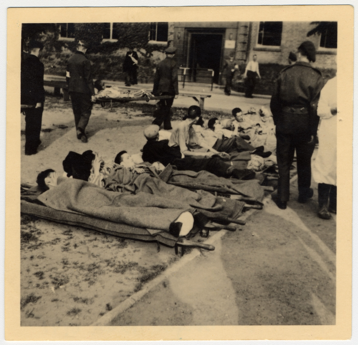 Infirmed survivors of Bergen Belsen lie on a row of stretchers while they wait to be attended to by British soldiers.