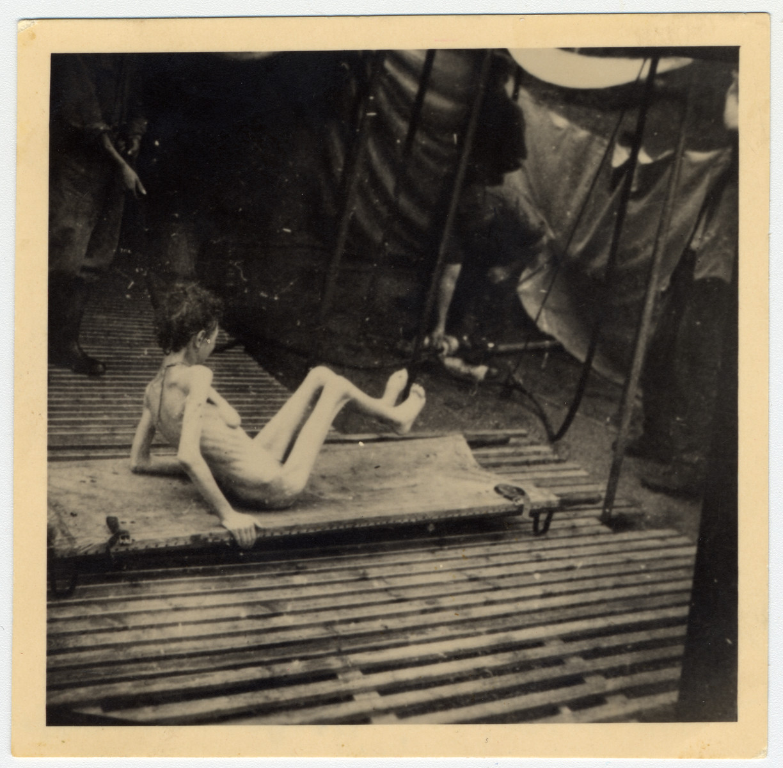 An emaciated survivor sits on a stretcher in Bergen-Belsen.