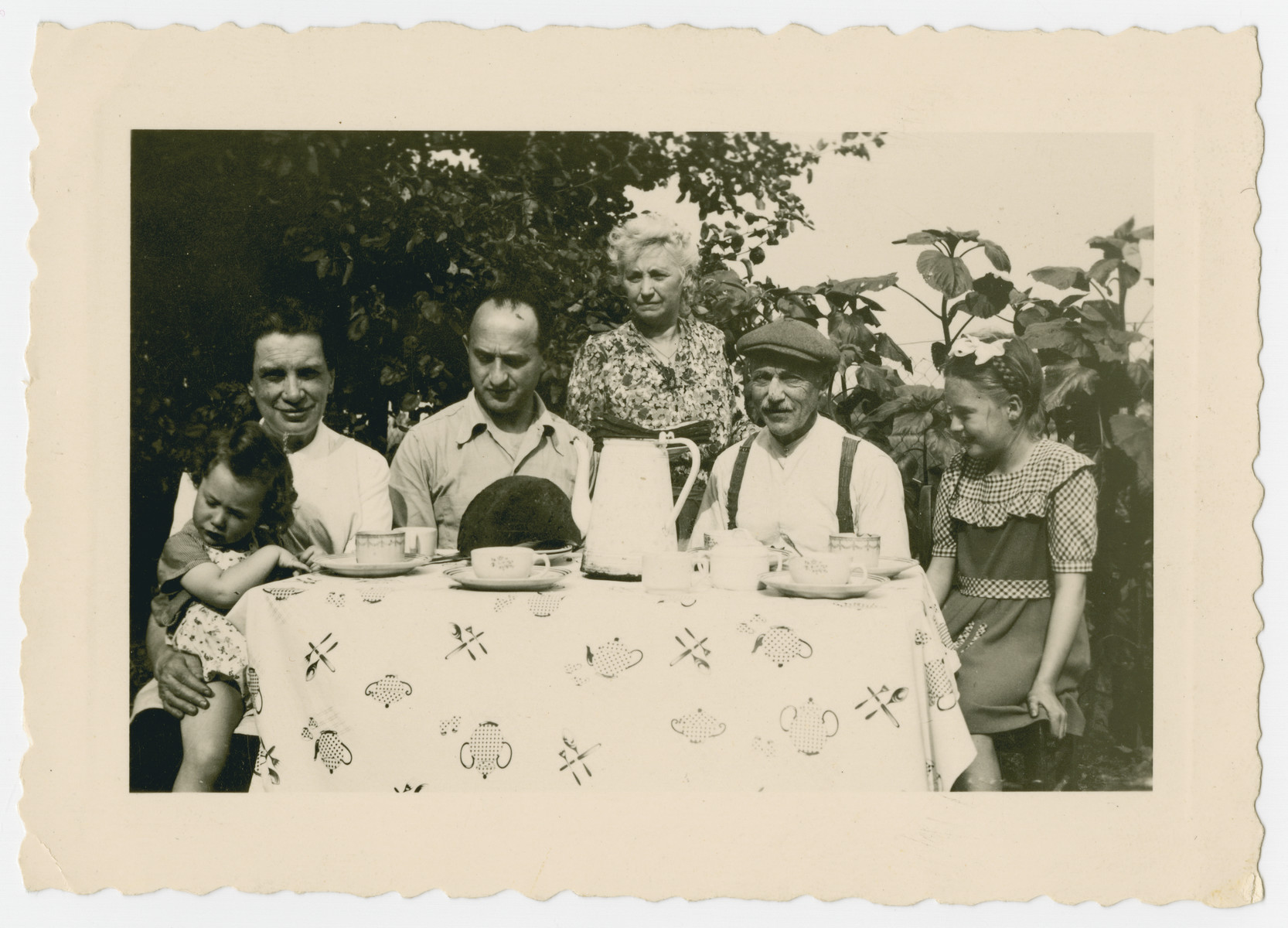 Shirley Gola sits at a table with her rescuers and family while in hiding.  Shirley Gola is seated on the lap of her rescuer Marie Fannes. Her father Joseph Gola is seated next to her.  Marrein, her godmother is standing next to her husband Monsieur Mal.  Their young niece is seated on the left.