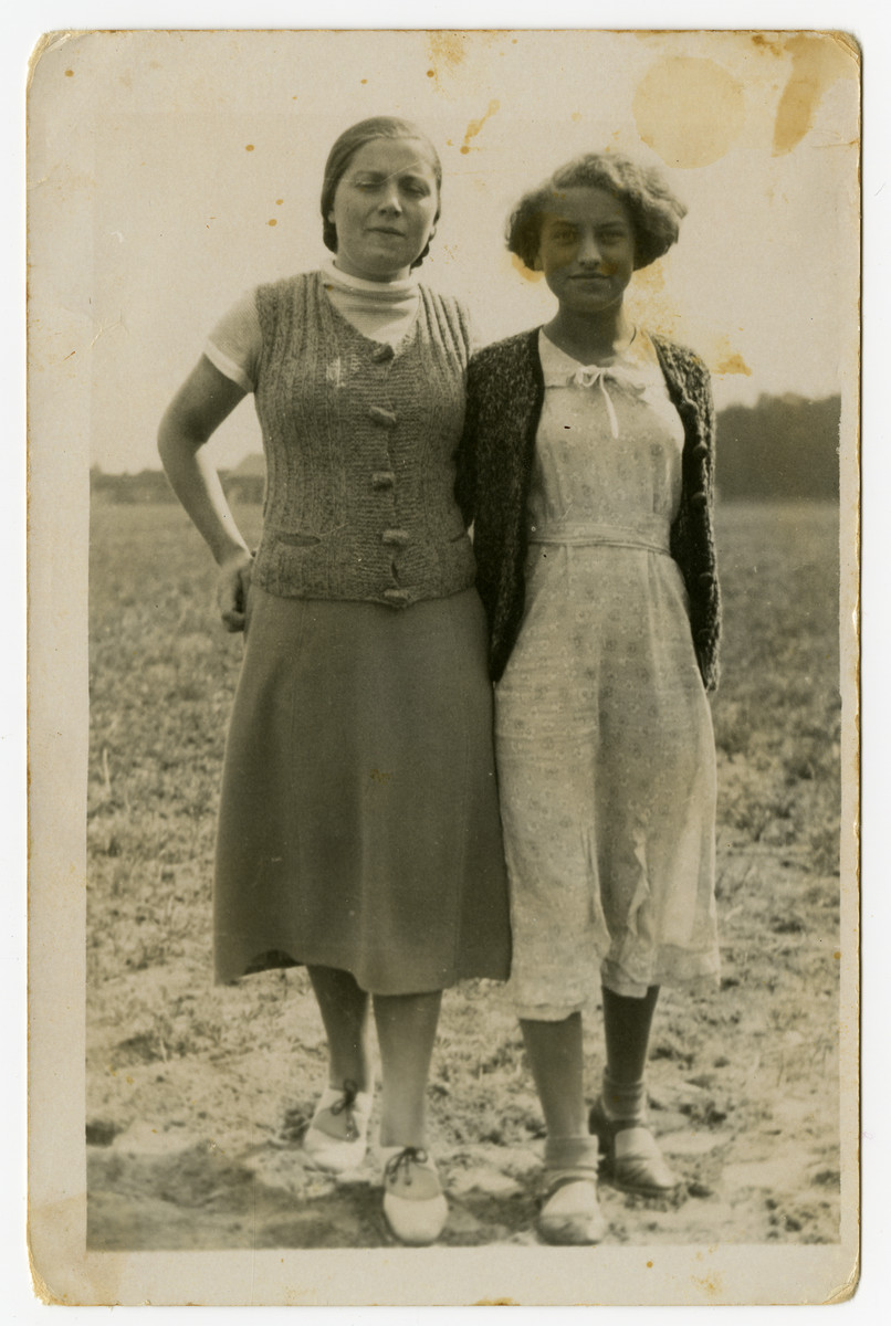 Portrait of sisters, Feiga and Rozka Grosman standing in an open field.