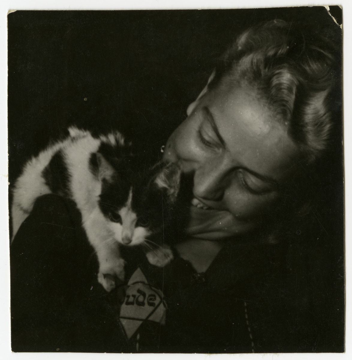 Rozka Grossman plays with a cat that she hid in her apartment in the Lodz ghetto.