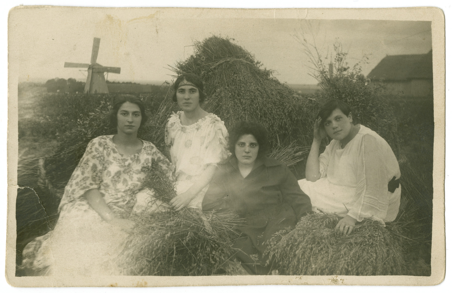 Four young Polish Jewish women sit amidst hay stacks.  Among those pictured are Rochel Katz (far left) and Chana Tykocka (second from left).