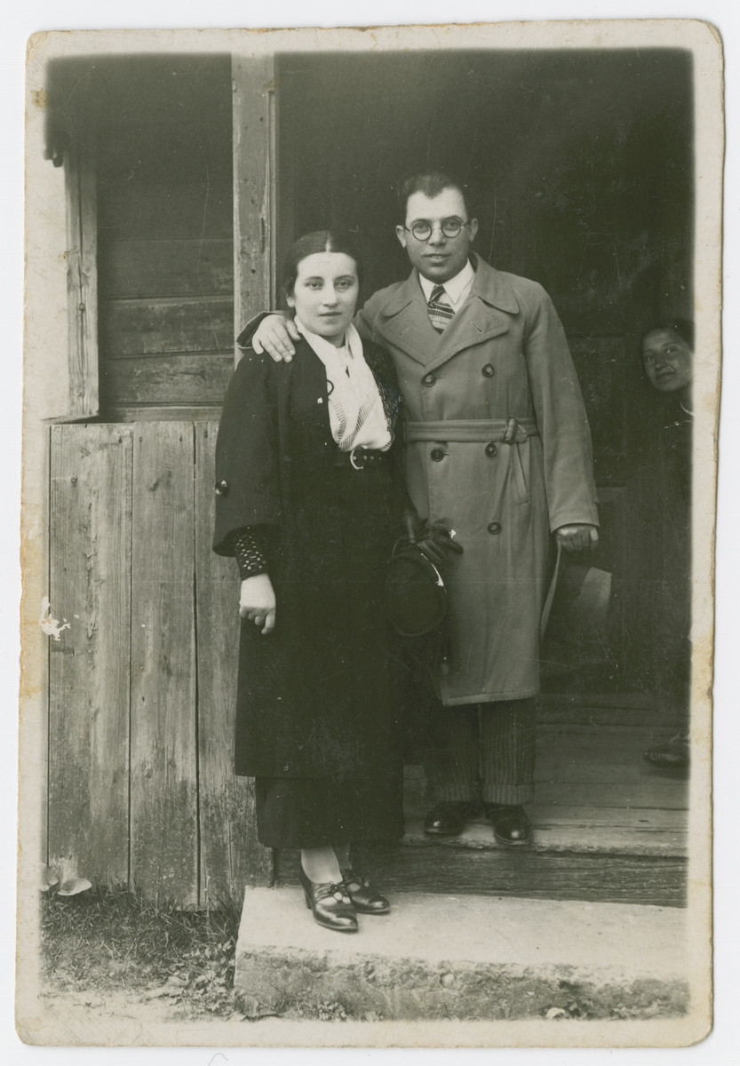 Nechama Schmidt and Efraim Tykocka  pose by the entrance to a wooden building.