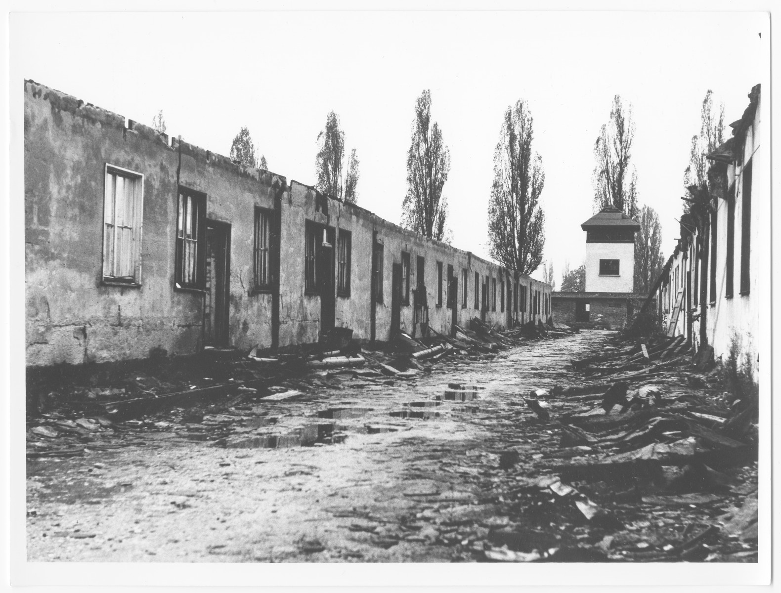 Postwar view of a barrack and watch tower in the Dachau concentration camp.