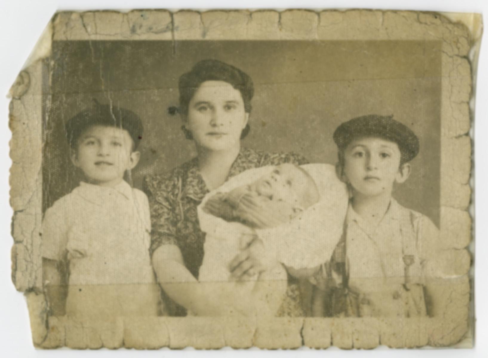 Ilona (Toba) Seidenfeld poses for a family portrait with her sons Ezra (left), Mordche (right), and Mojsche.