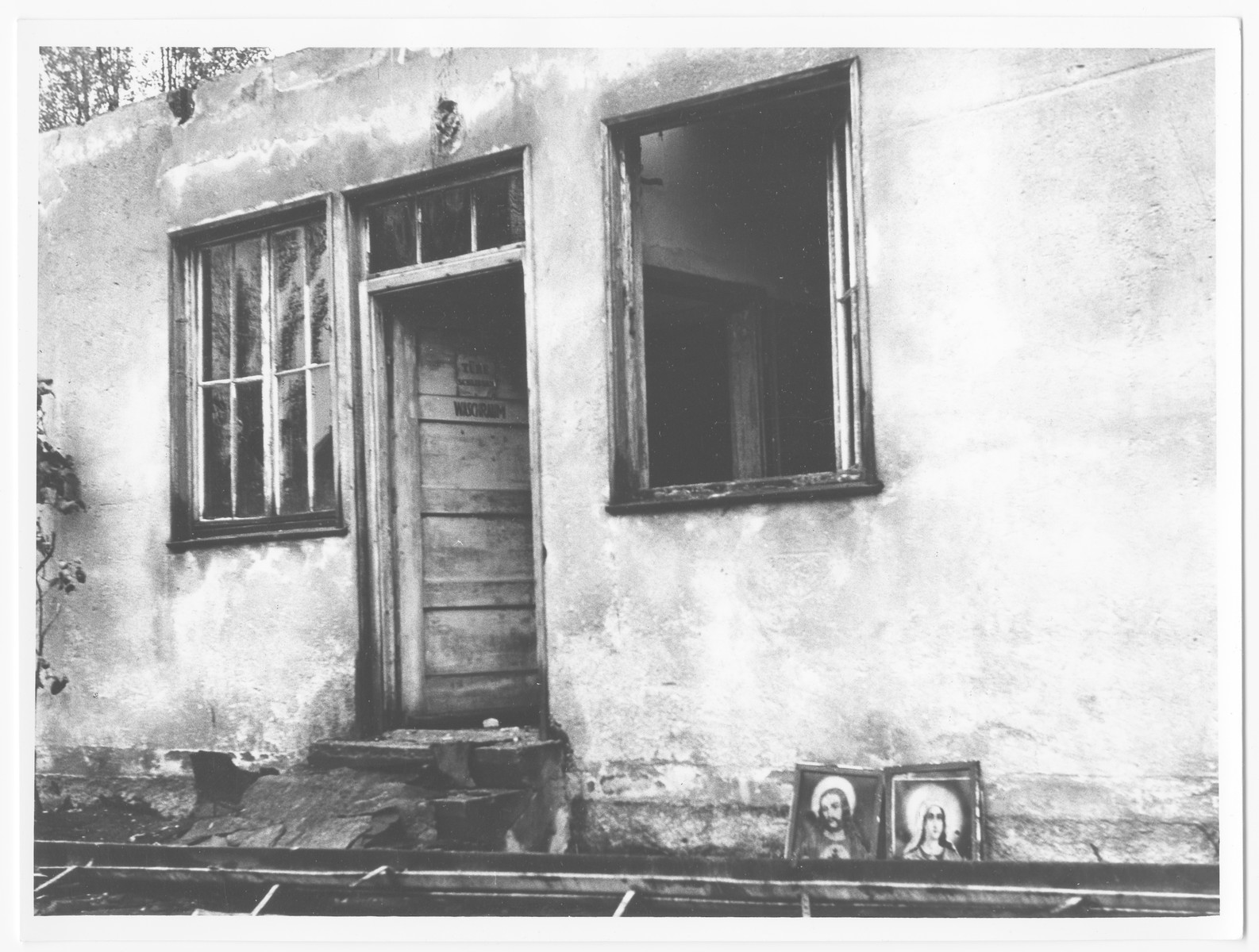 Postwar view of a barrack in Dachau with portraits of Jesus and Mary propped up against it.