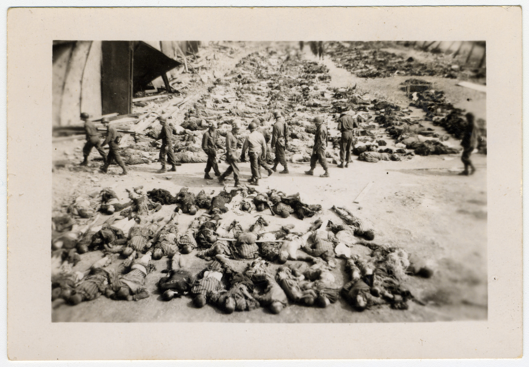 American soldiers walk among corpses that are laid out in rows in the Nordhausen concentration camp.