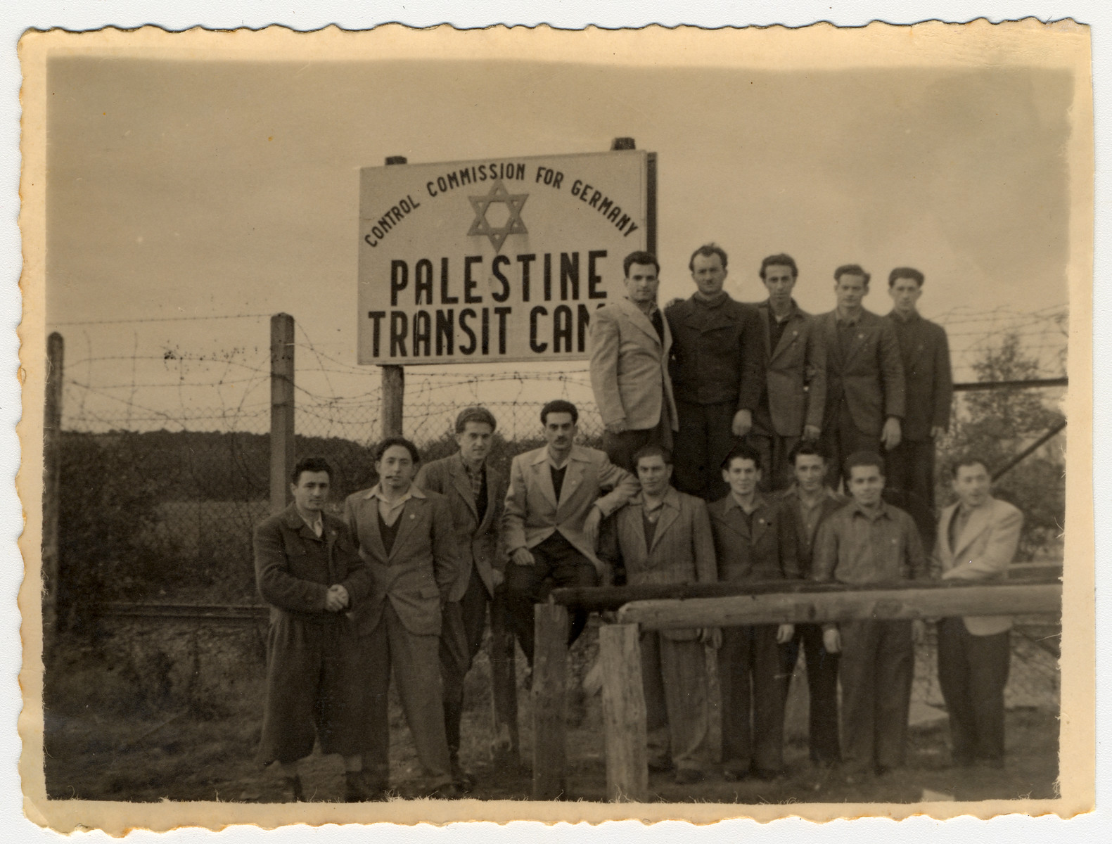 Jewish men pose by the sign at the Palestine Transit Camp prior to their leaving Germany for Palestine.