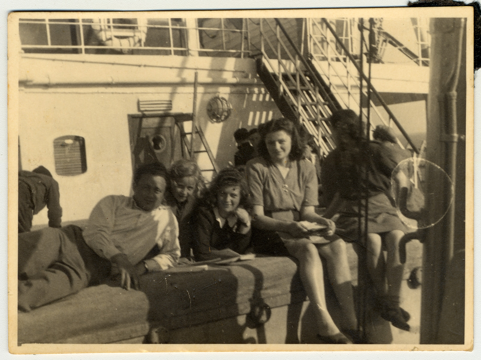 """Former passengers from the Exodus relax on board The Transylvania where they are immigrating """"legally"""" to Palestine with certificates provided by the Bricha.  Pictured in the center with a book is Sara Wiener."""