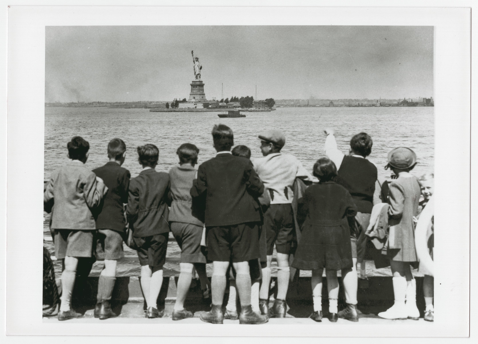 Children aboard the President Harding look at the Statue of Liberty as they pull into New York harbor.  They were brought to the United States by Gilbert and Eleanor Kraus.