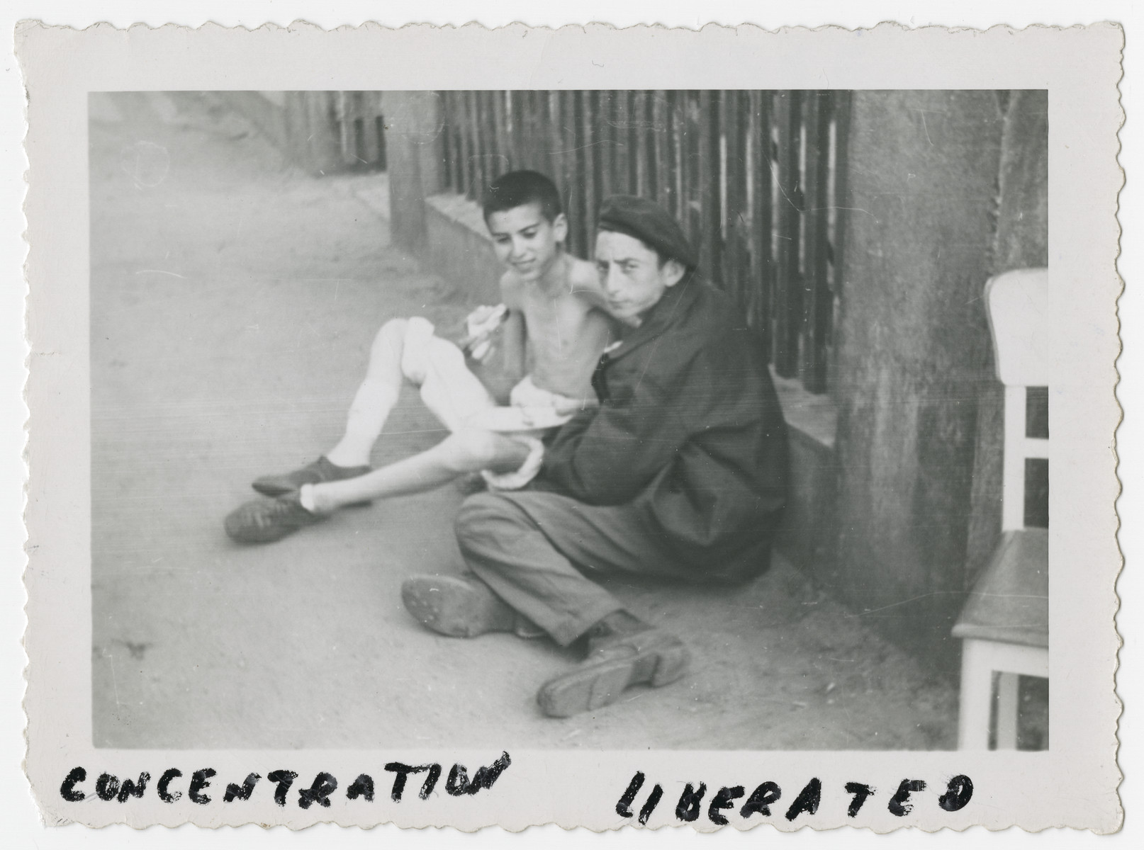 Two young prisoners from the Woebbelin concentration camp lean against a fence after liberation.    The one farthest from camera was interned at age 15 and was liberated at age 18.  He weighed 60 lbs when liberated.