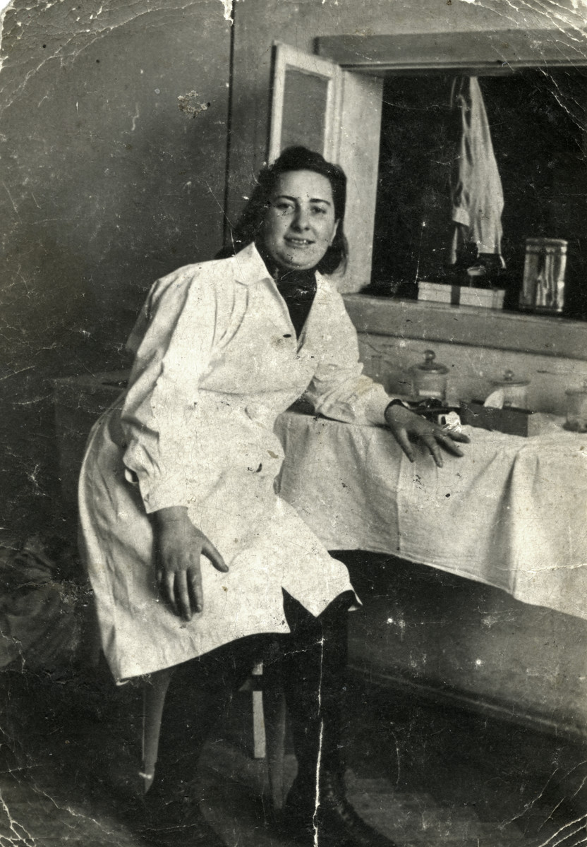 Sara Szajfman sits in the hospital of the Kielce ghetto wearing her nurse's coat.  A friend of Sara's took this photograph and hid it in his shoe during his stay in Auschwitz. He later gave it to the Sara in the 1960s.