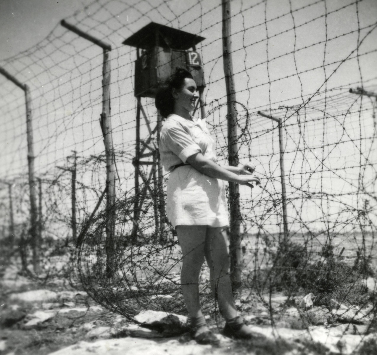 Sara Szajfman stands next to the barbed wire fence surrounding the detention camp in Cyprus.