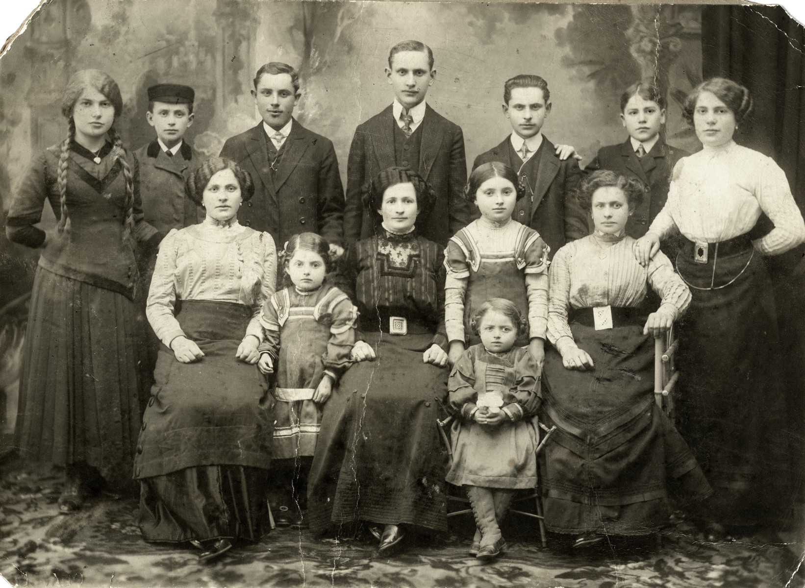 Studio portrait of Szajfman family.  Among those pictured are Tsvetle (Chaim Leichter's mother, standing far right) and Benjamin Szajfman (father of Sara), standing third from the right).  His brother Eliezer is to his left.