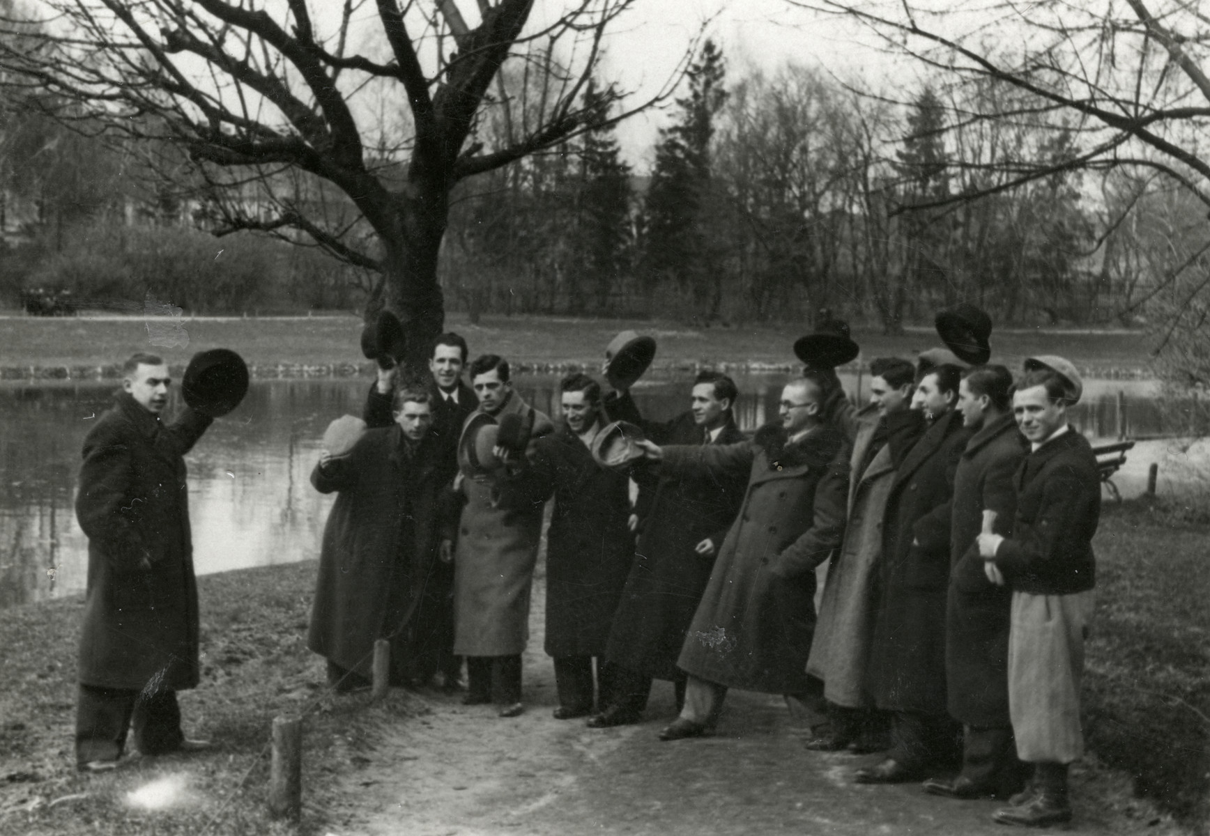 A group of friends waves their hats in a farewell to Isaac Rembichowski, who was leaving for Cuba.   He later came to the United States.  Chaim Leichter is pictured second from the left.
