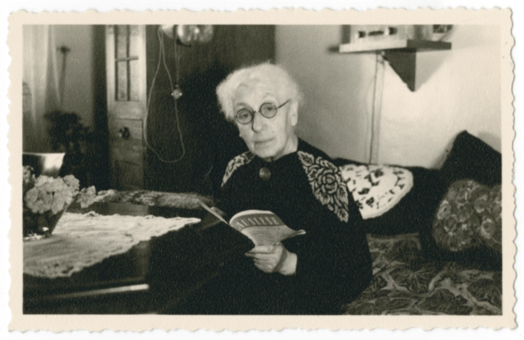 Regina (nee Kottlarzig) Brieger reads a book in her apartment in the Jewish Hospital in Iranischestrasse, Berlin iwhere Ilse visited her.             Regina Brieger  survived incarceration in Theresienstadt where she had worked as a nurse, albeit without proper medication or supplies.
