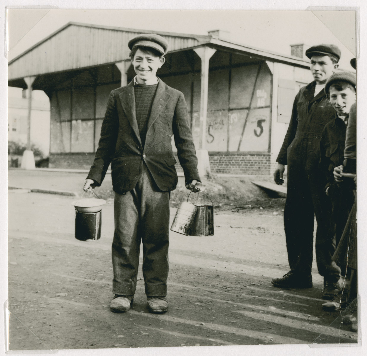 "A young man carries lunch pails in each hand outside barrack #5 in the Ziegenhain displaced persons camp.  The original captions reads: ""How they eat in Zeigenhain."""