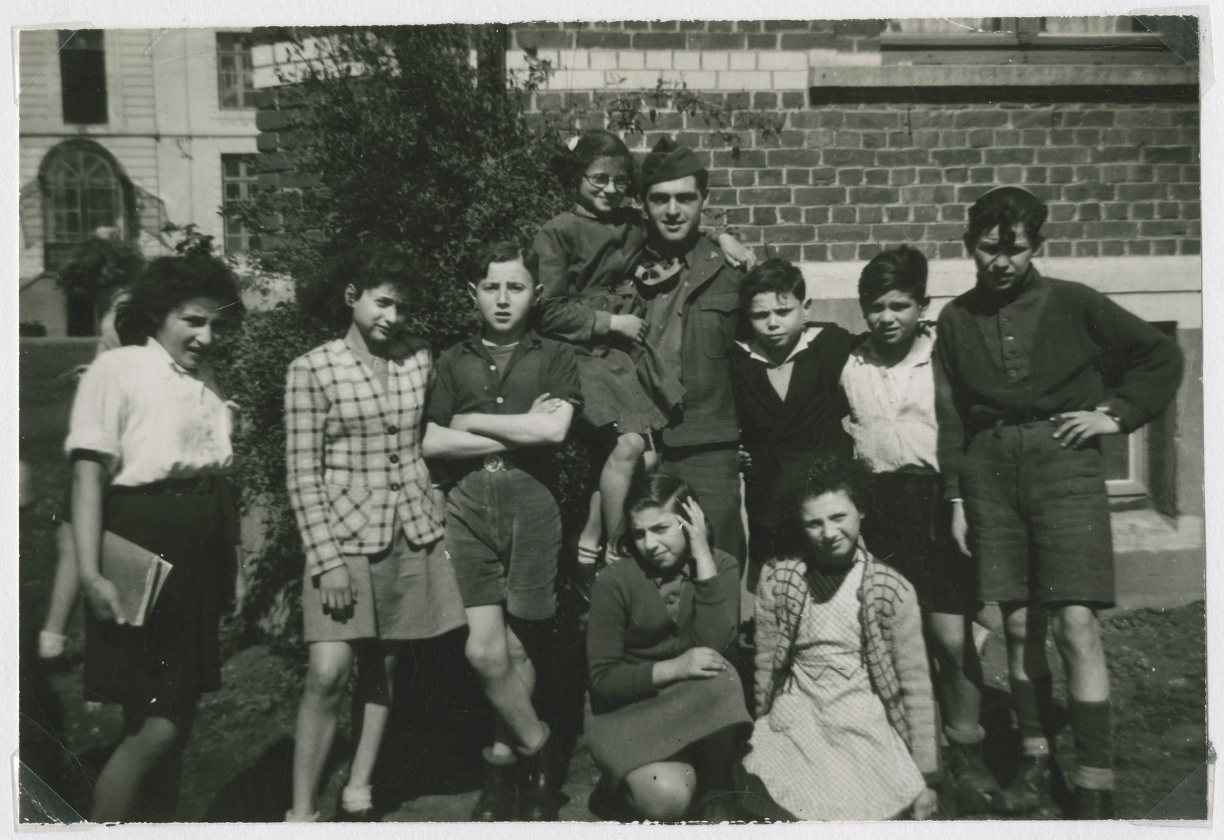 """David Marcus poses with Jewish children in Marquain, Belgium.  The original caption reads: """"Marquain,  Hachsharah.  How children look when comparatively well cared for in a free country.  I just had to get in a pictured with these lovely Jewish children.  They asked for and got a high speed drive with me in my jeep."""""""