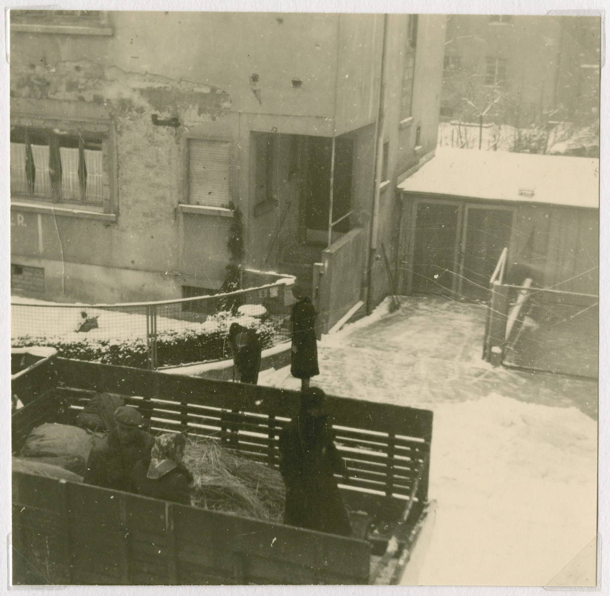 "An open truck is parked in the Ziegenhain displaced persons camp in the snow.  The original caption states: ""Truck from Ziegenhain waiting for Council supplies to be loaded on it."""