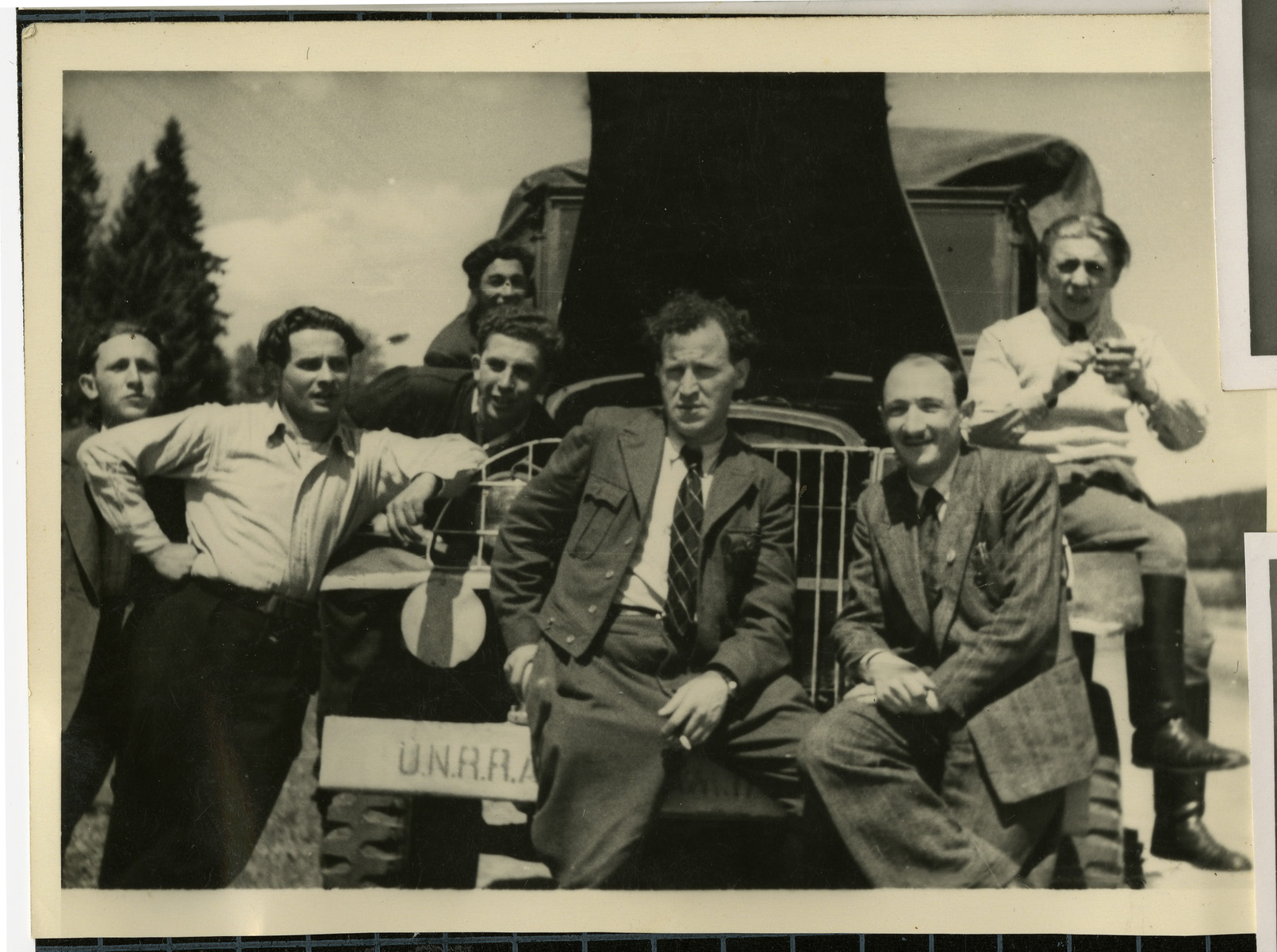 Members of the Bamberg Yiddish Theater group gather around a truck laden with props as they prepare to perform a play in a neighboring displaced persons camp.  Solomon Zynstein, the director, is seated on the right.