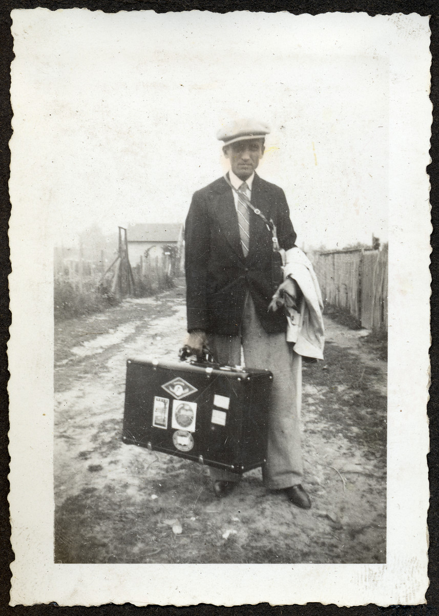 Portrait of a man [possibly Philip Roiter] carrying a suitcase down an unpaved road in an unidentified locale.  This is one photograph from the album of Rosalia Dratler Roiter.  She later was deported to and perished at Auschwitz.