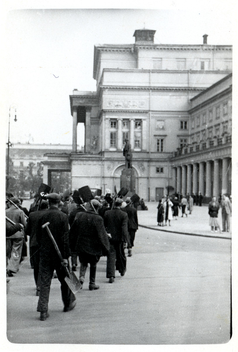 Polish men march past the Great Theatre in Warsaw to dig anti-tank trenches against the German Army.