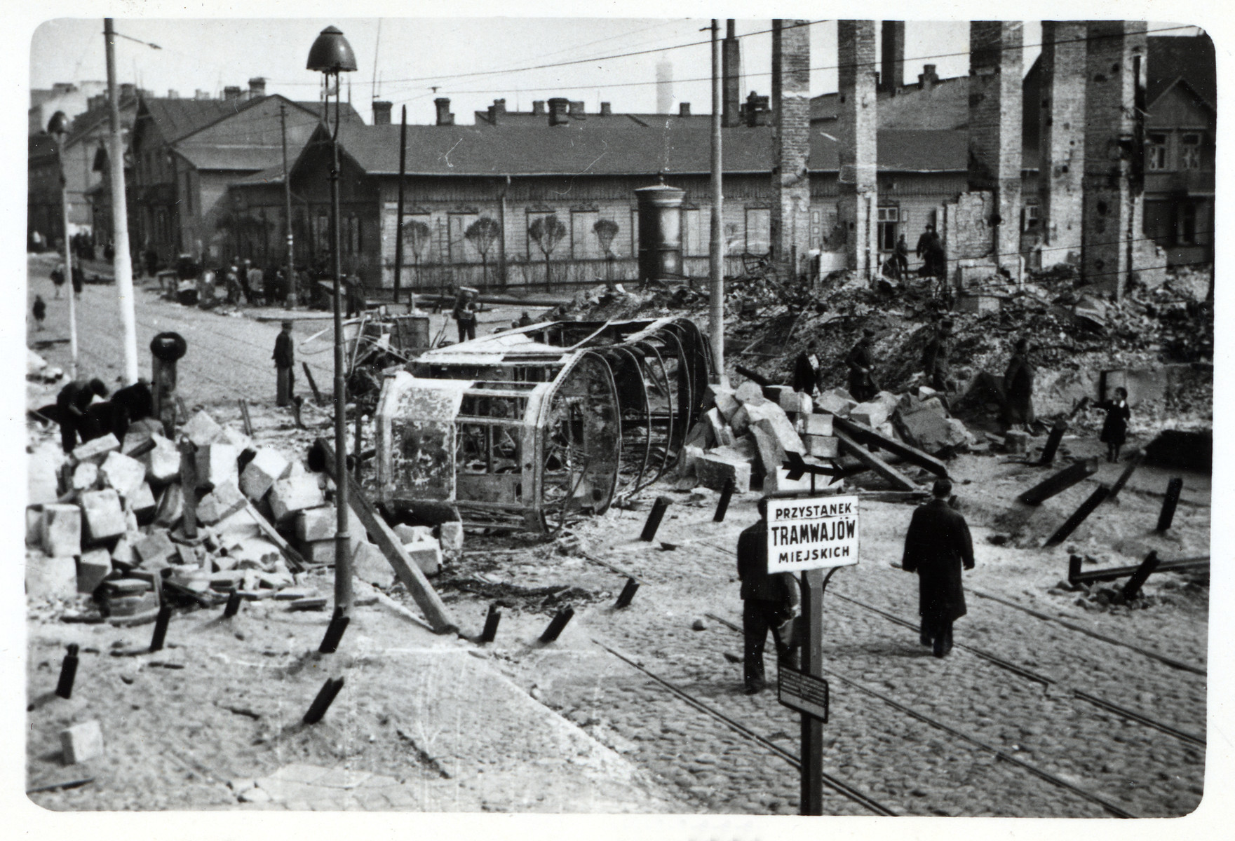 View of a destroyed streetcar on a bomb damaged street in besieged Warsaw.