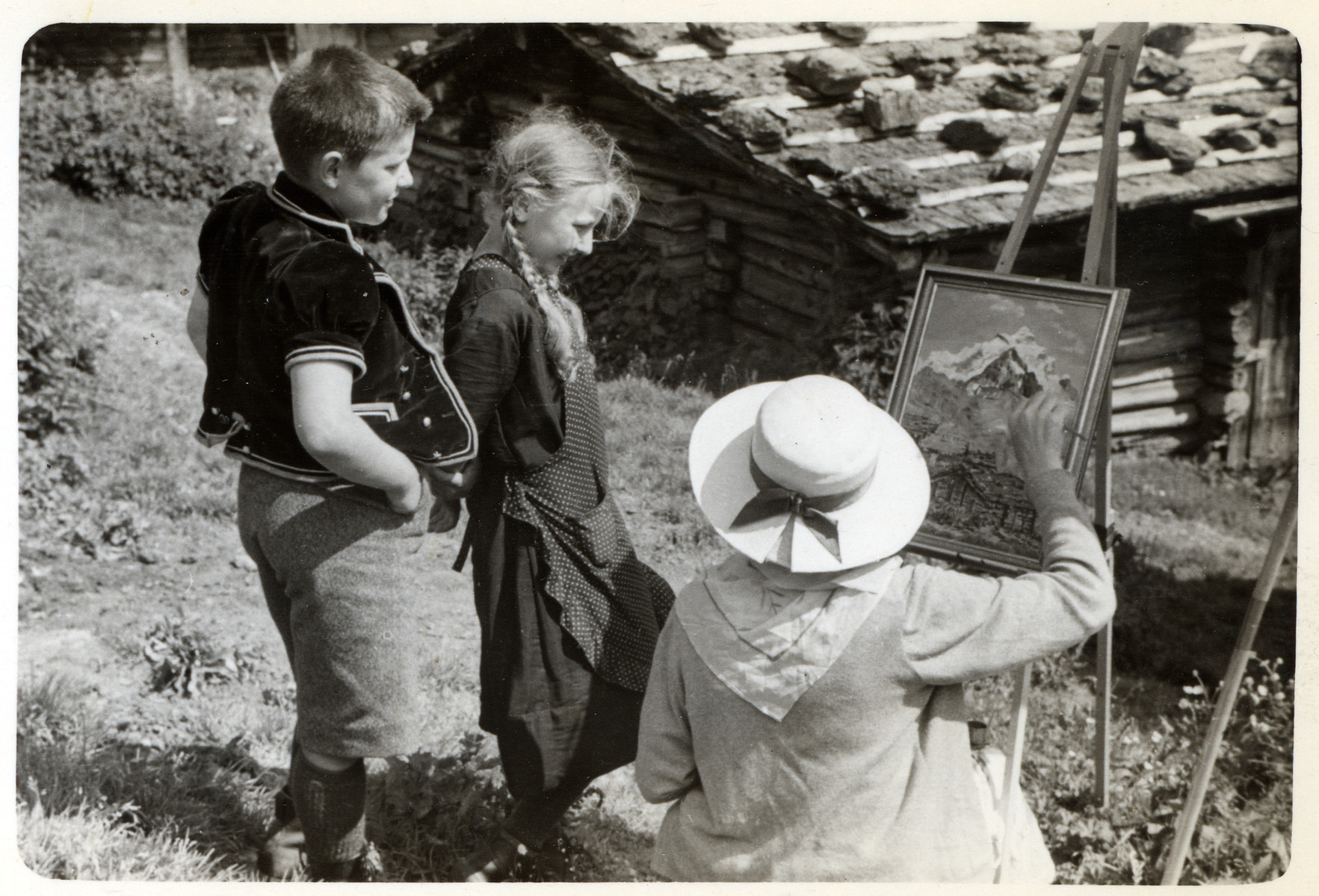 A woman paints a landscape while two young children look on.