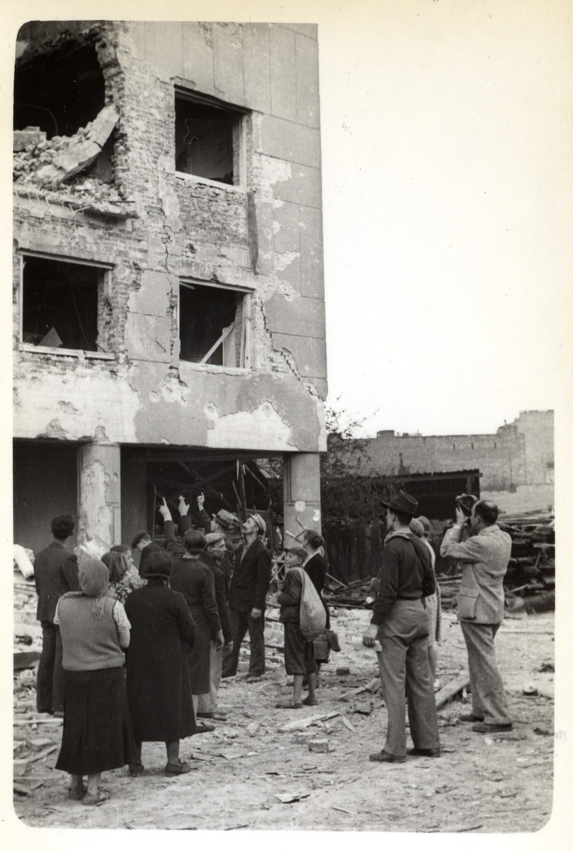 Polish citizens observe a destroyed building in besieged Warsaw while Julien Bryan films the scene.