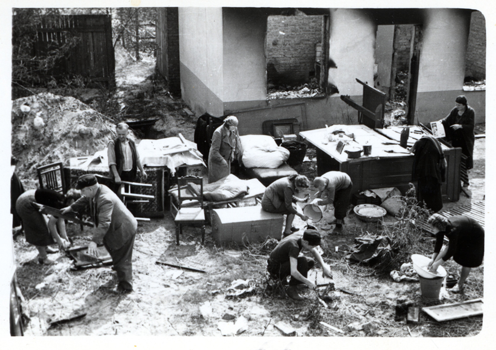 View from above of a Polish family performing their daily chores amidst the remnants of their household furnishings that they have reassembled outside the charred ruins of their home in Warsaw.  The boy with the hatchet is Albert Turowski, who later became a film actor in postwar Poland.