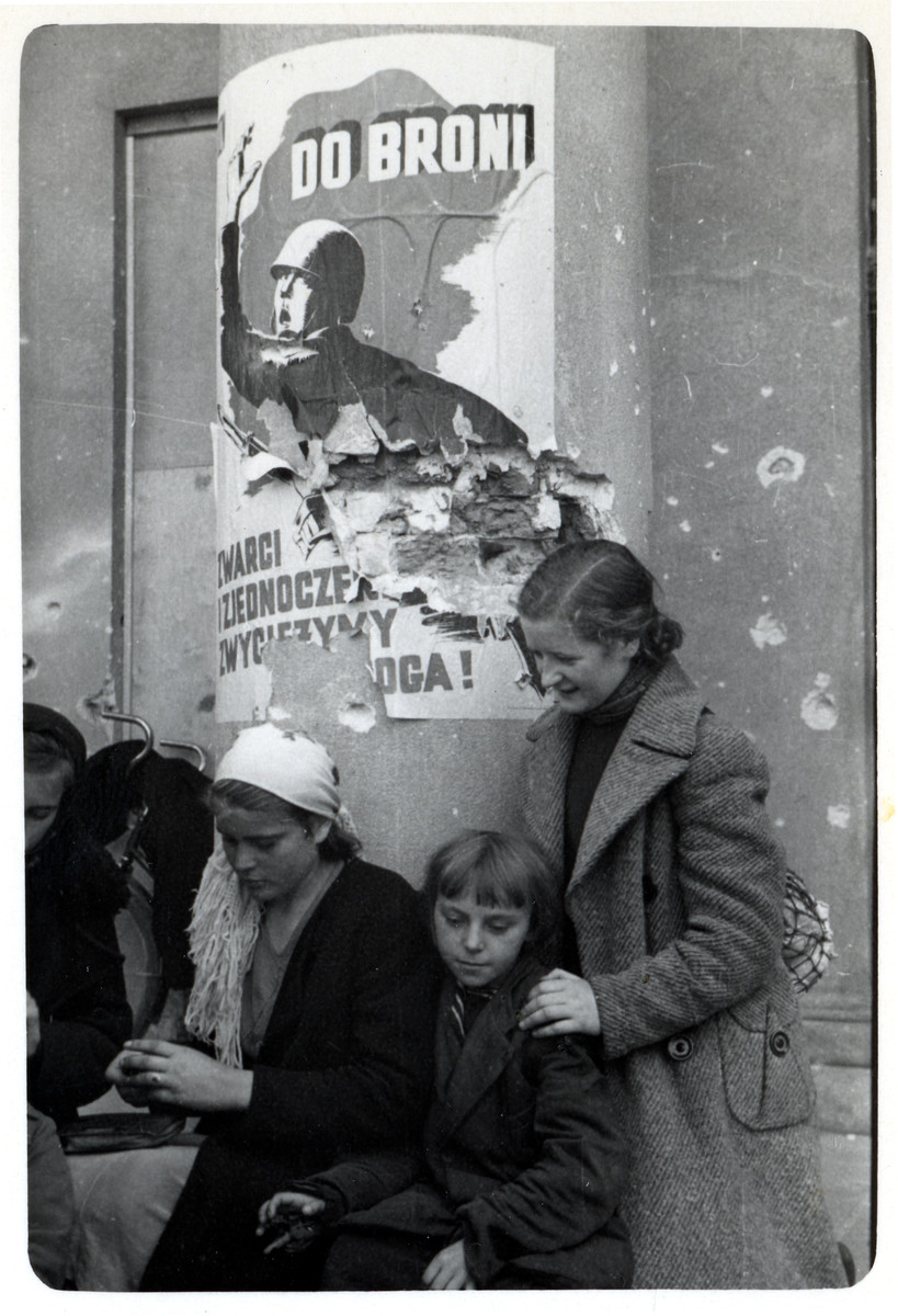 A Polish family huddles around a column in front of the Opera House in besieged Warsaw.