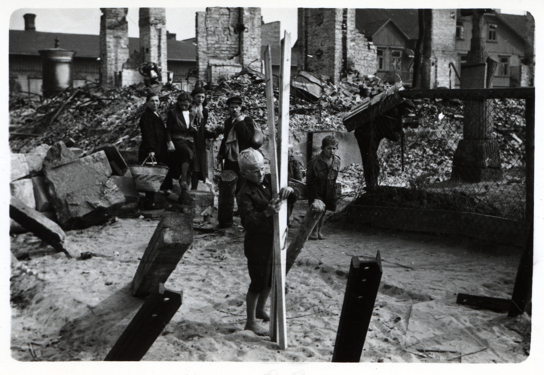 Polish women and children venture into bombed-out and besieged Warsaw to find wood for fuel.