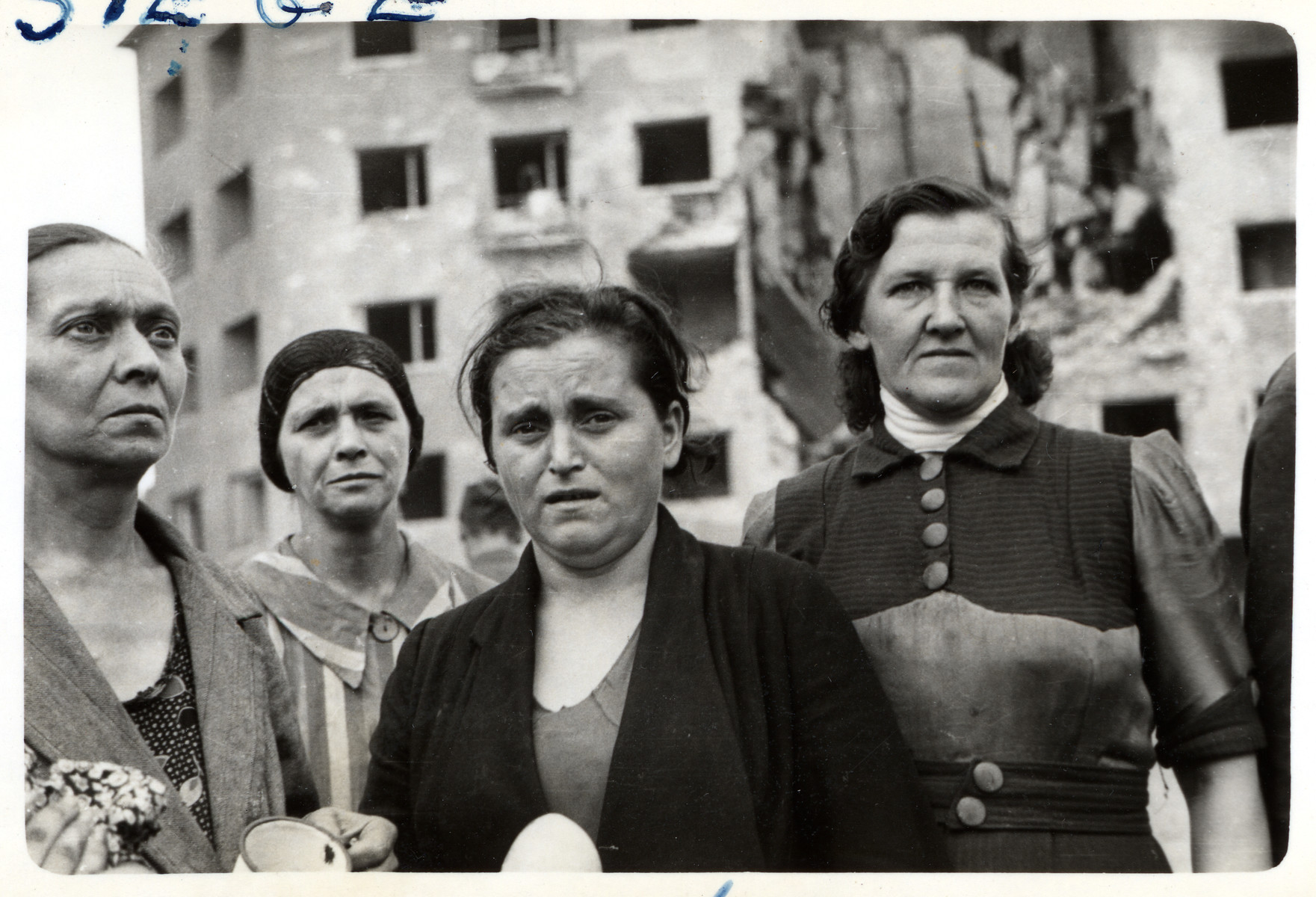 A group of Polish women stare ahead in front of a bombed out building in besieged Warsaw.