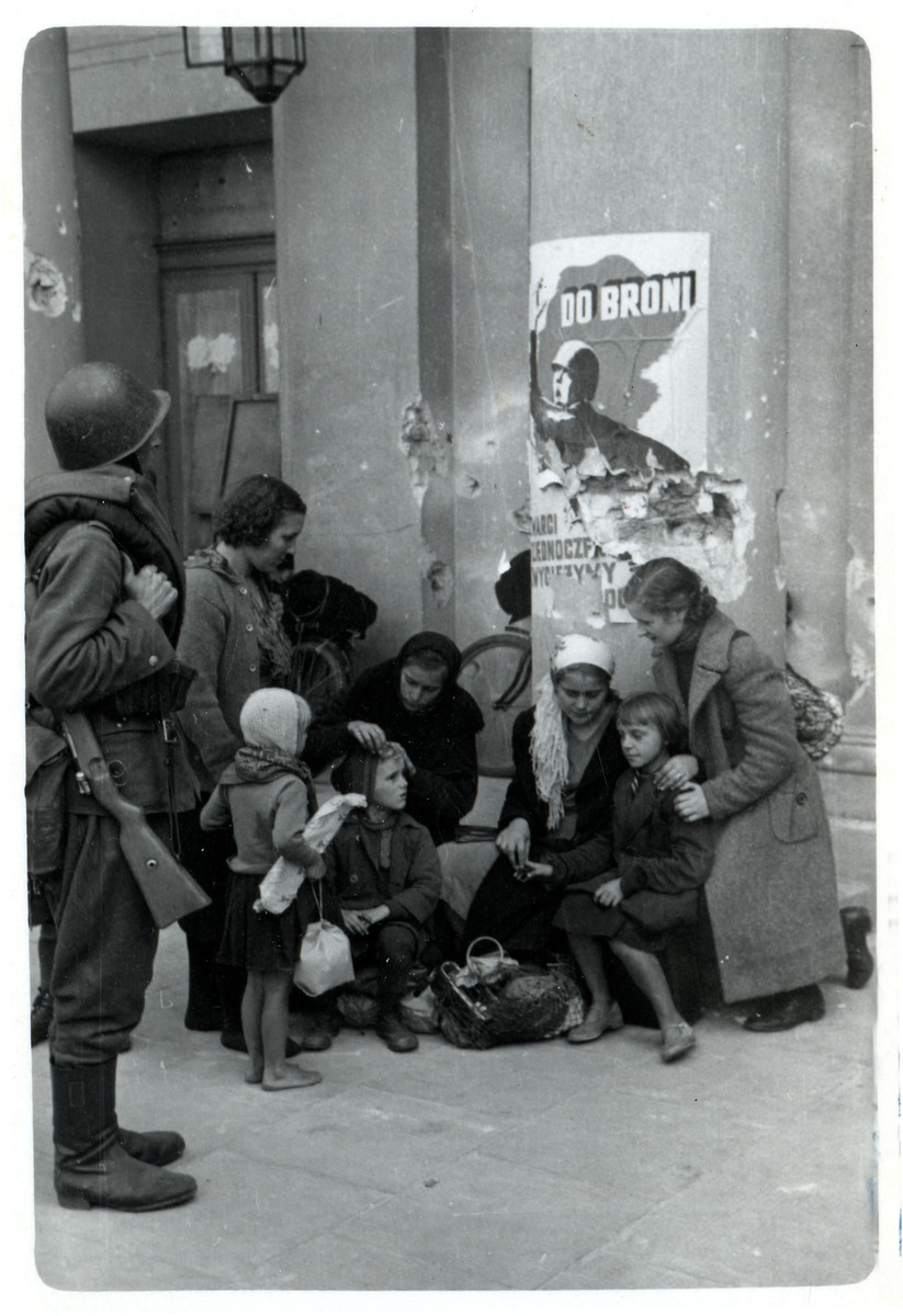 A Polish family huddles around a column in front of the Opera House in besieged Warsaw while a Polish soldier looks on.