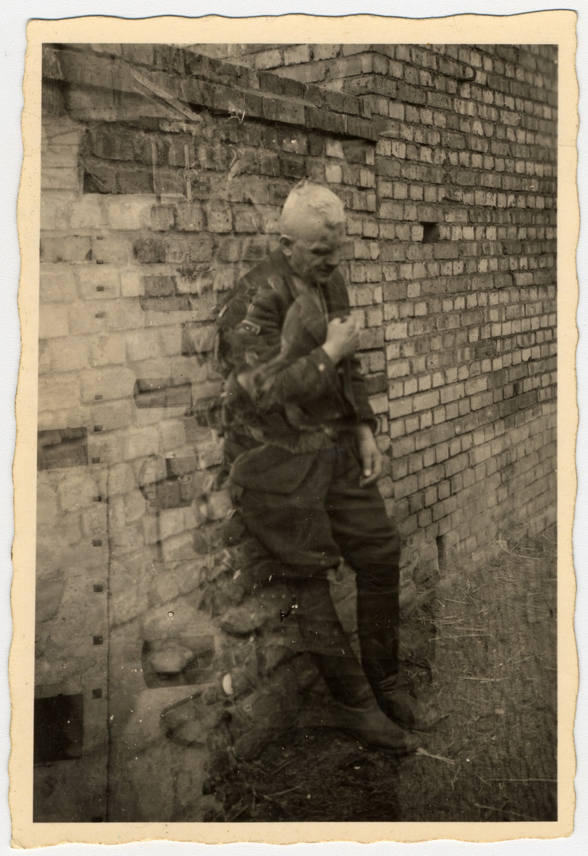 "An SS officer who was beaten up by Poles and Russians leans against a brick wall.    The original caption reads "" Tanennberg, Germany Here is an S.S. leader, after some Poles & Russians had beaten him up. He is the type who tortured slave laborers & forced reluctant German soldiers to continue a lost fight. Turn the picture sideways and you will see some of the soldiers who were under his command. It looks as though he has a photograph conscience!"""