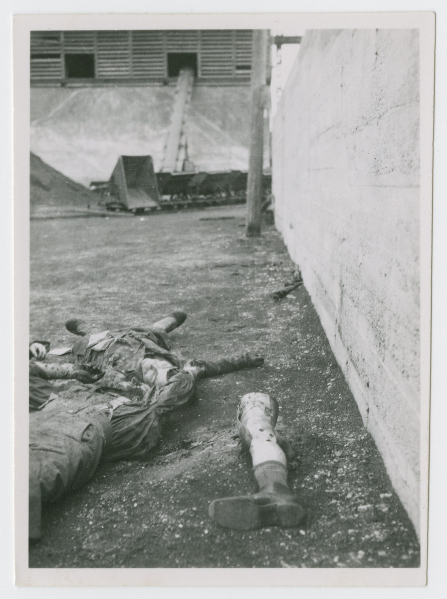 """Bodies of SS men lie on the ground of the camp after American soldiers shot them.  The original caption reads"""" Wooden leg of SS man and another after killed."""""""