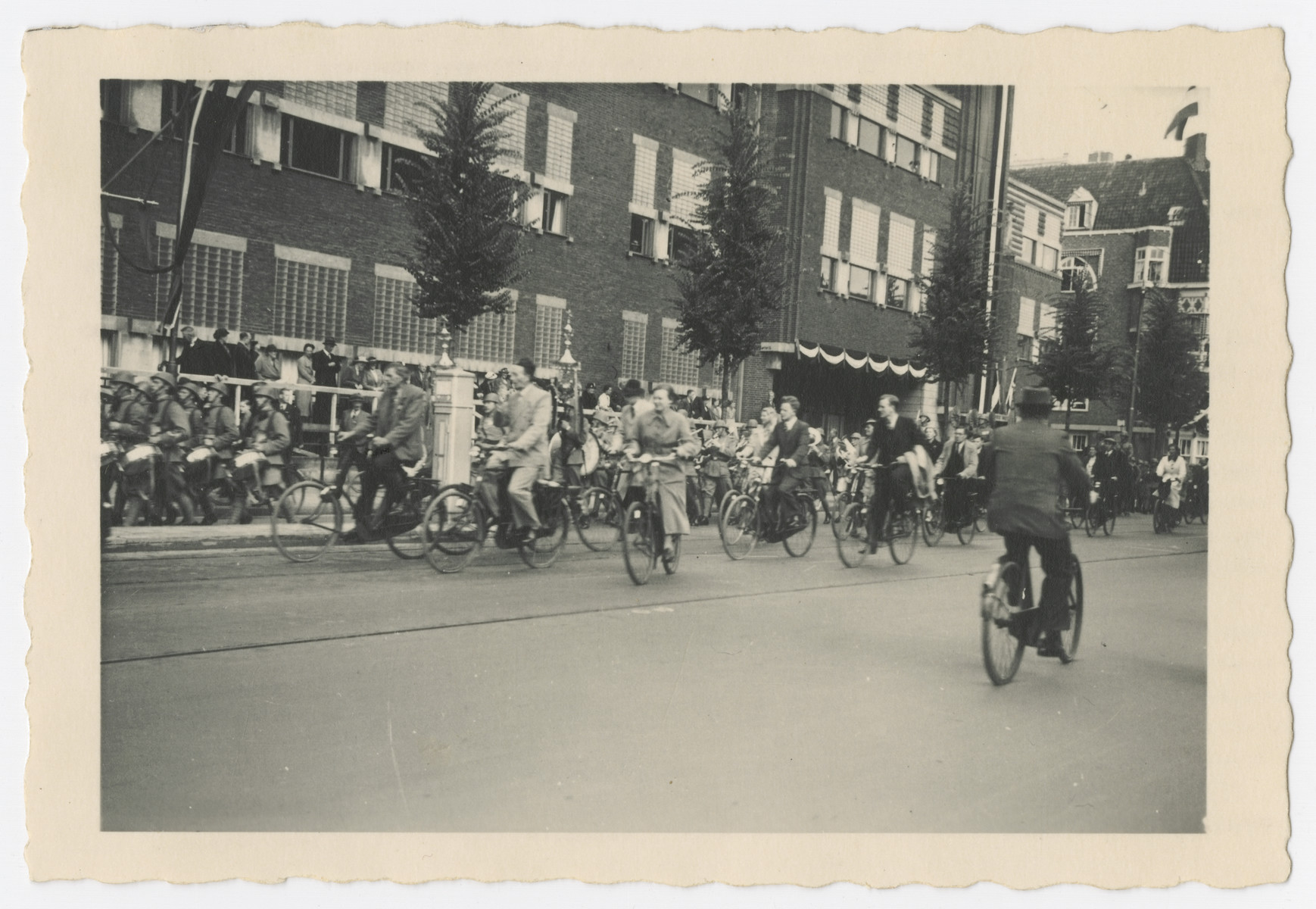 Dutch citizens ride their bicycles during the celebration of the 40th anniversary of Queen Wilhelmina's reign.