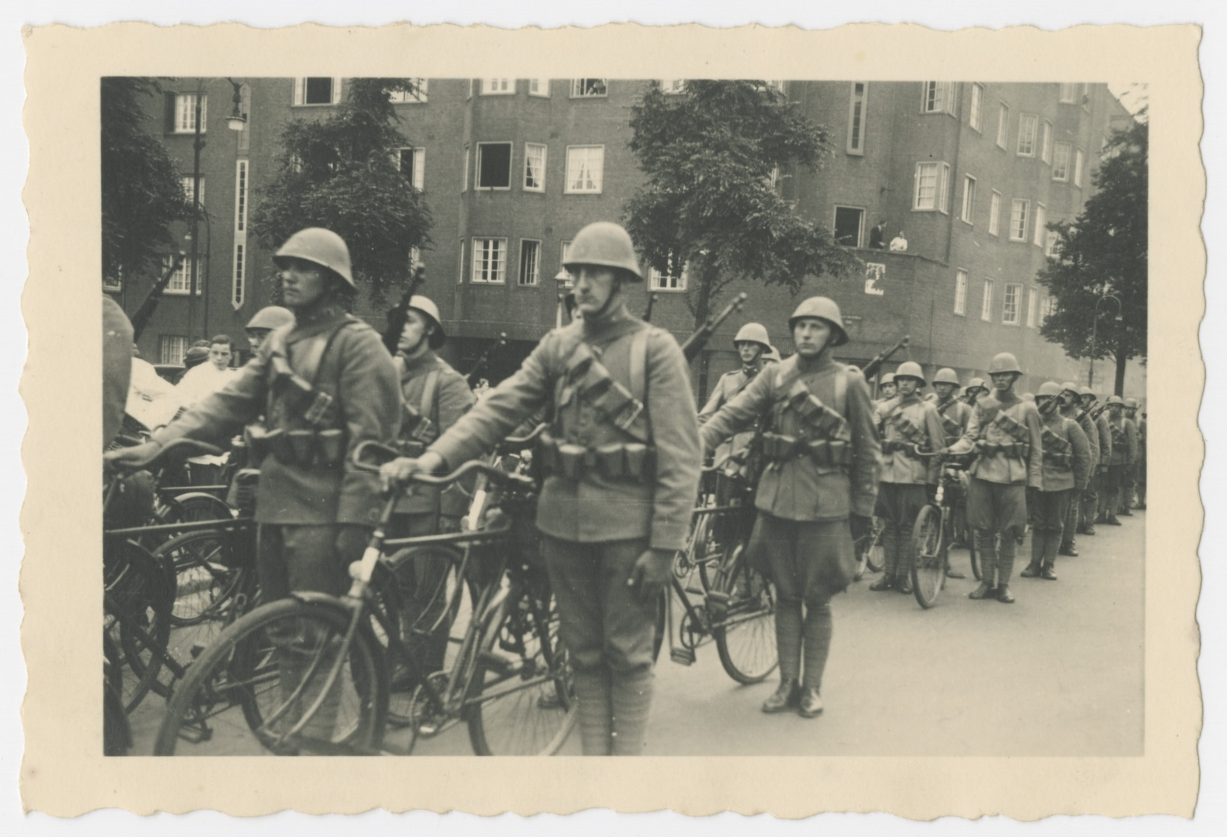 Dutch soldiers parade with their bicycles during the celebration of Queen Wilhelmina's 40th year on the throne.