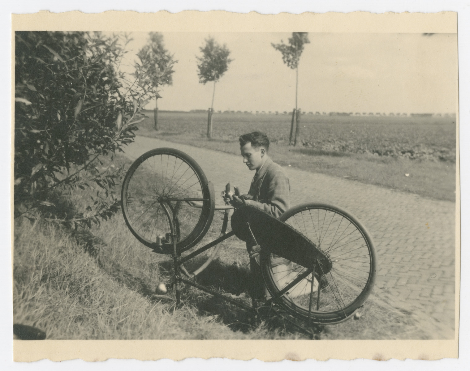 Louis Baars repairs his bicycle by the side of a road.