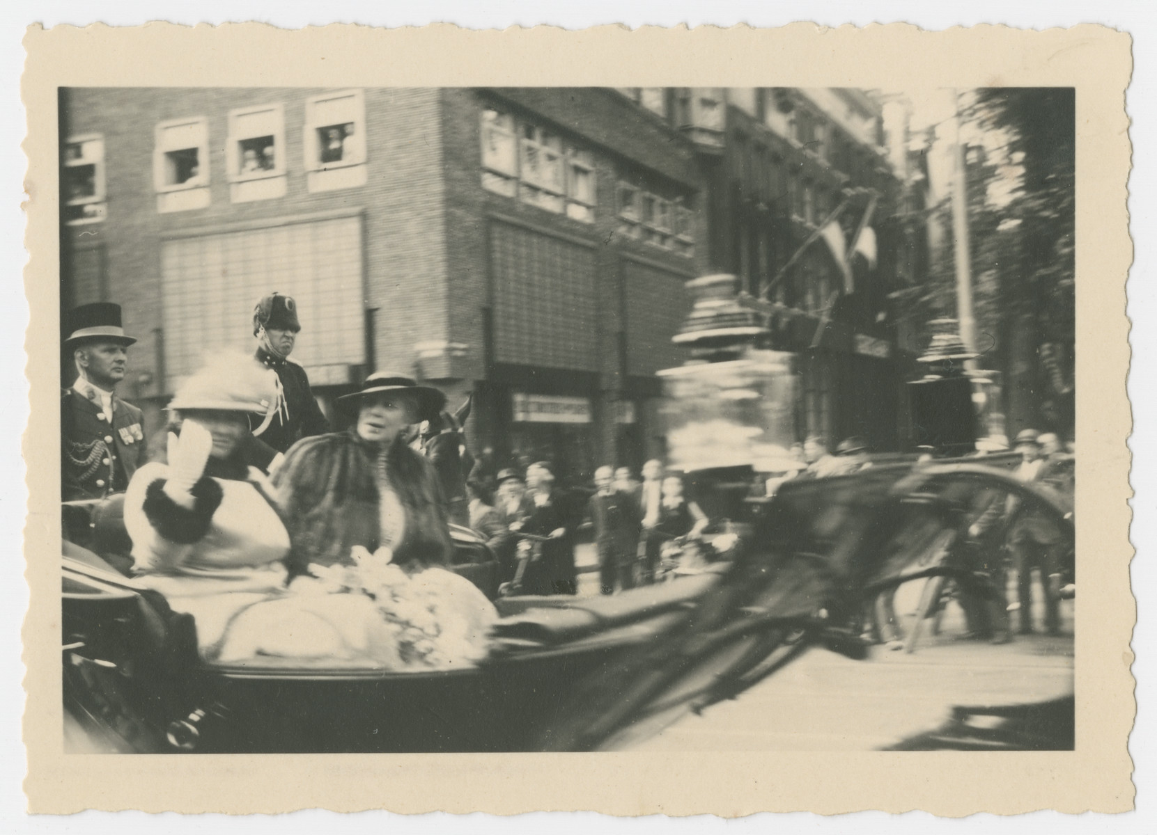 Queen Wilhelmina rides in an open automobile during a celebration marking her 40th year on the throne.