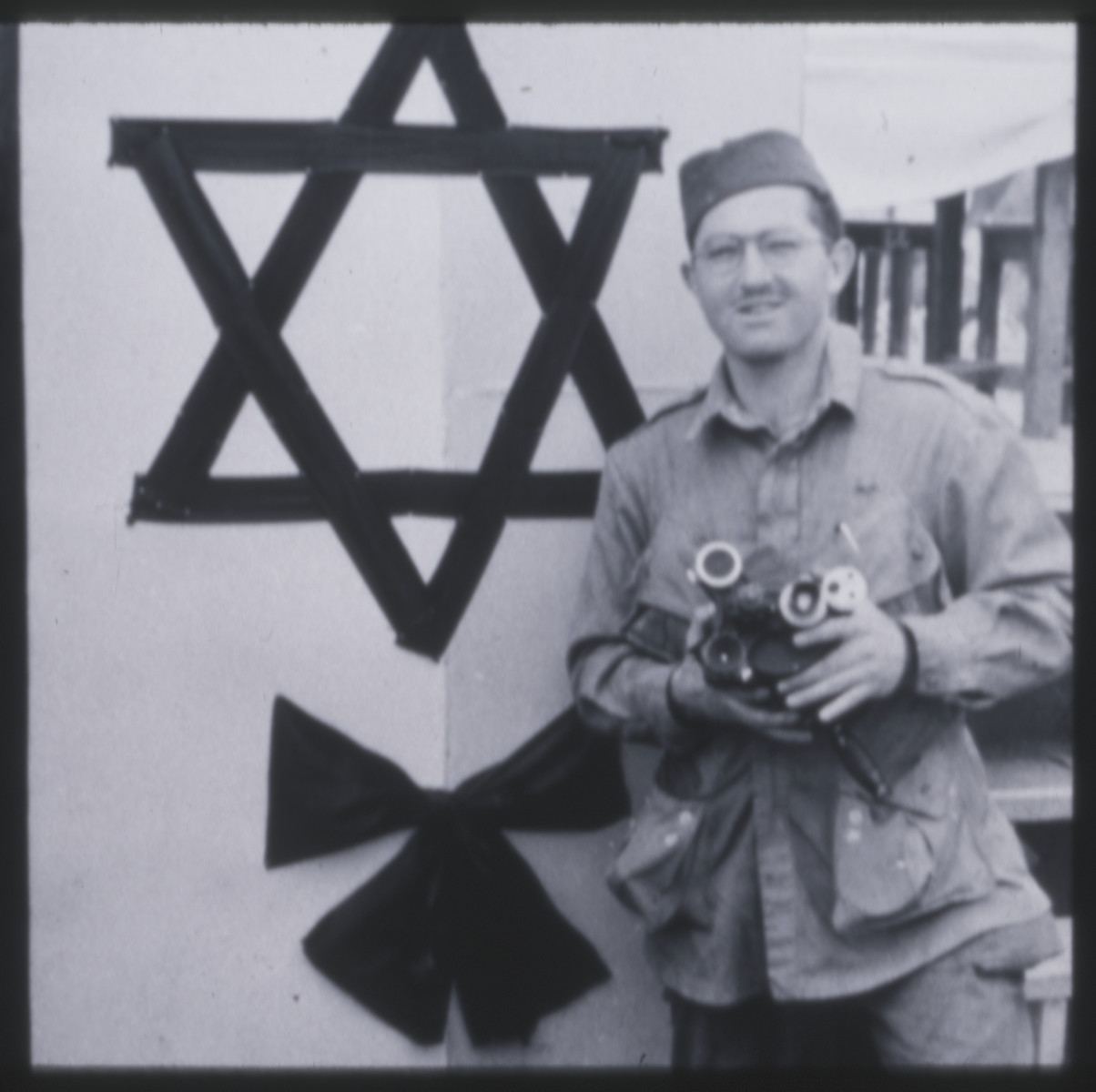 Portrait of photographer Phil Drell standing with his camera in front of a large Jewish star erected for the Dachau camp memorial.
