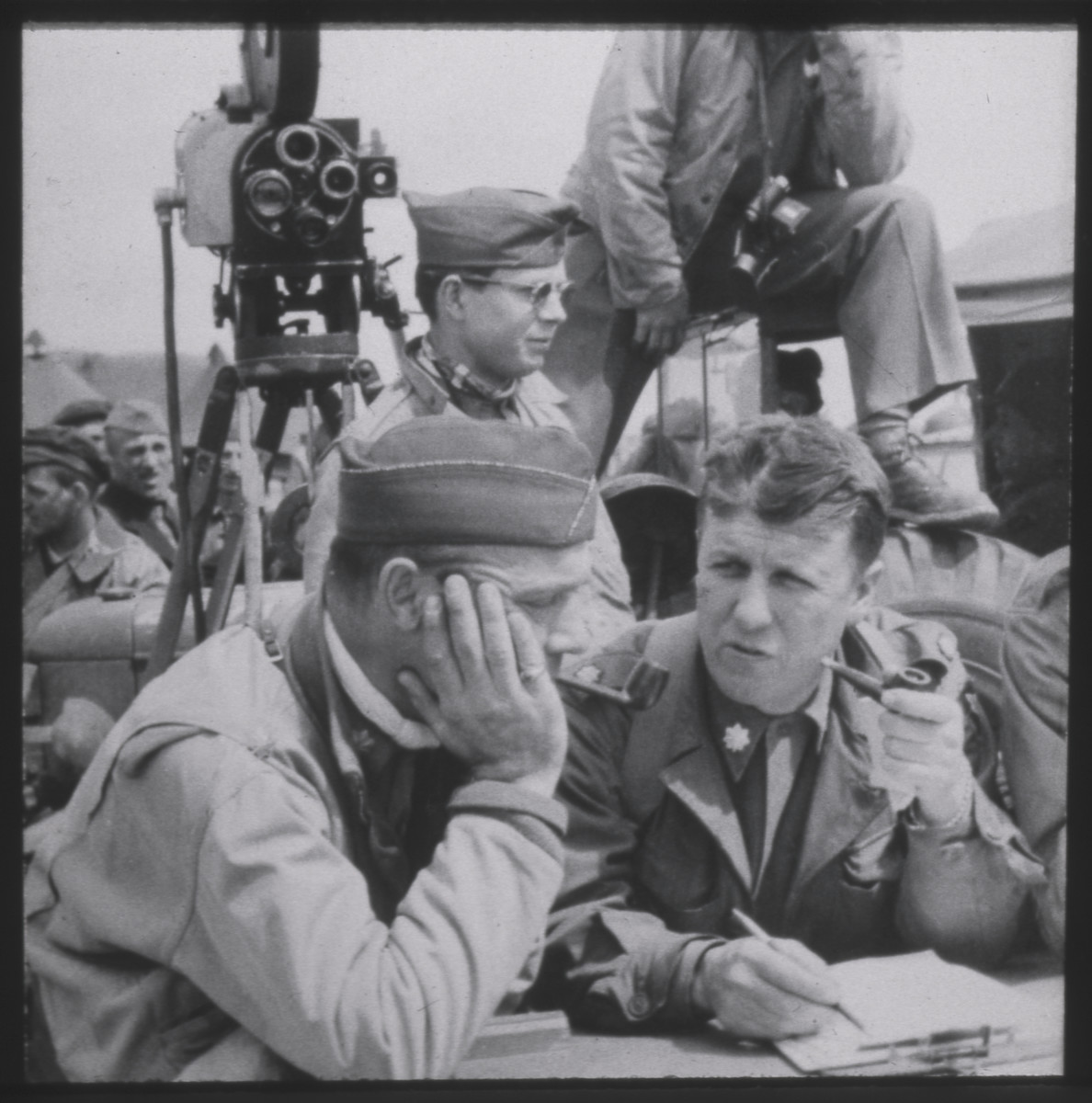 Members of the SPECOU group (Special Motion Picture Coverage Unit) of the Allied Expeditionary Force compile a report.  Seated with pencil and clipboard is George Stevens.