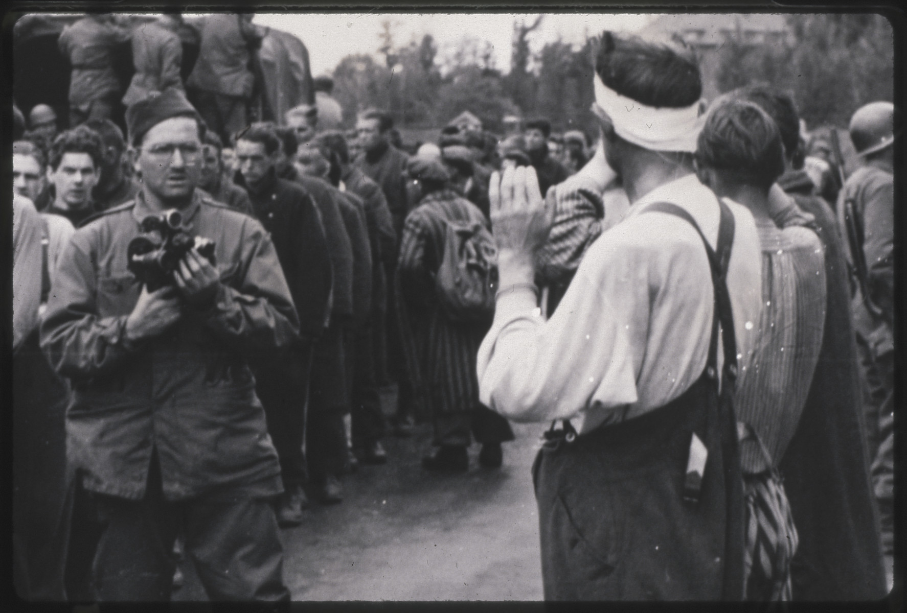Philip Drell takes photograhs of the surrender of Dachau camp guards while liberated prisoners look on.