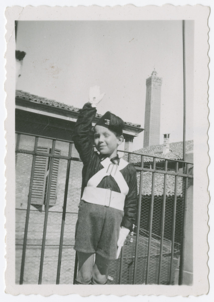 Daniele Nacamu, dressed in the uniform of Figlio della Lupa, gives a Fascist salute on the terrace of his home in Bologna.  This was the Fascist youth group for very young boys up to age 8.  From 1933 whoever was enrolled at primary school was a member. After the imposition of the Racial Laws In 1938 Jews could no longer belong.