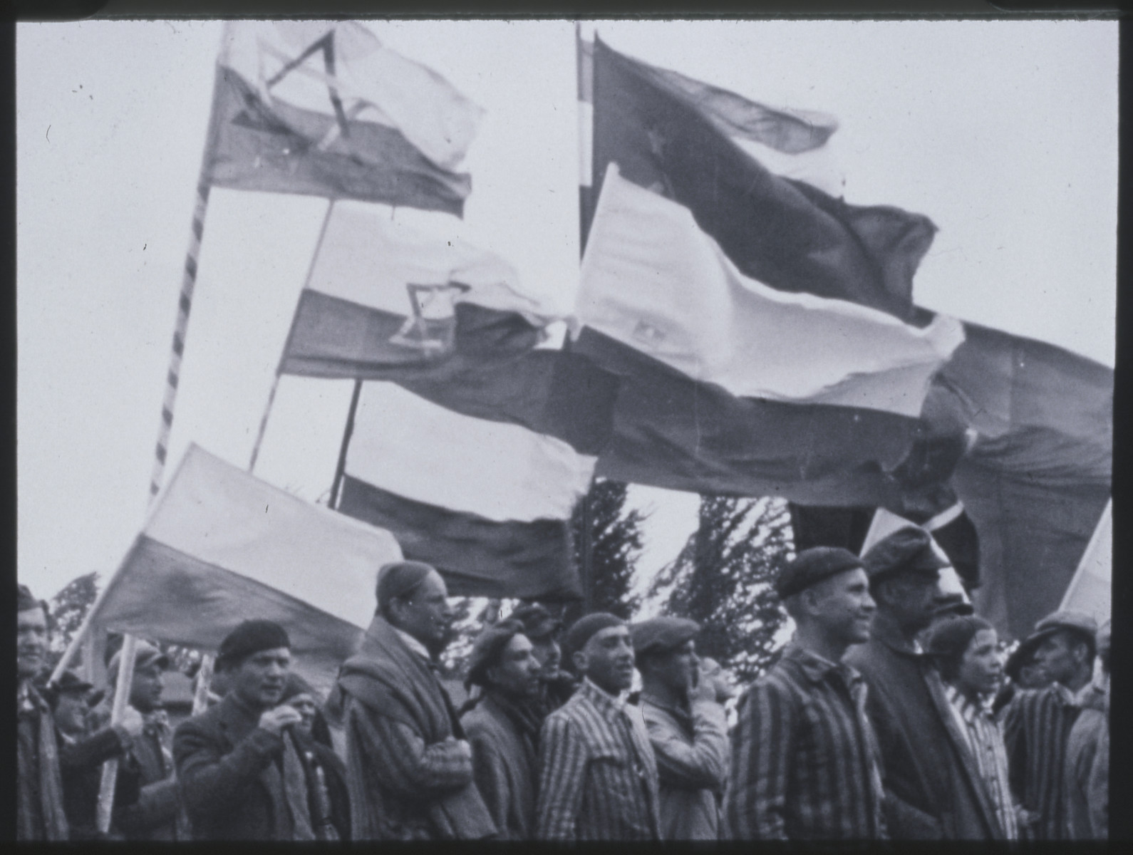 Survivors of the Dachau concentration camp gather for a memorial service after liberation.  They hold flags for various nationalities; Zionist flags can be seen on the left.