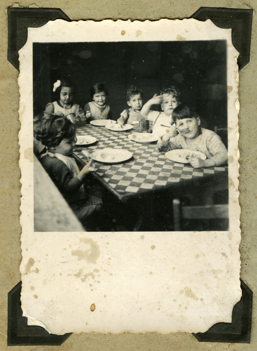 Children at the Nos Petits children's home in Belgium are seated around a table eating.