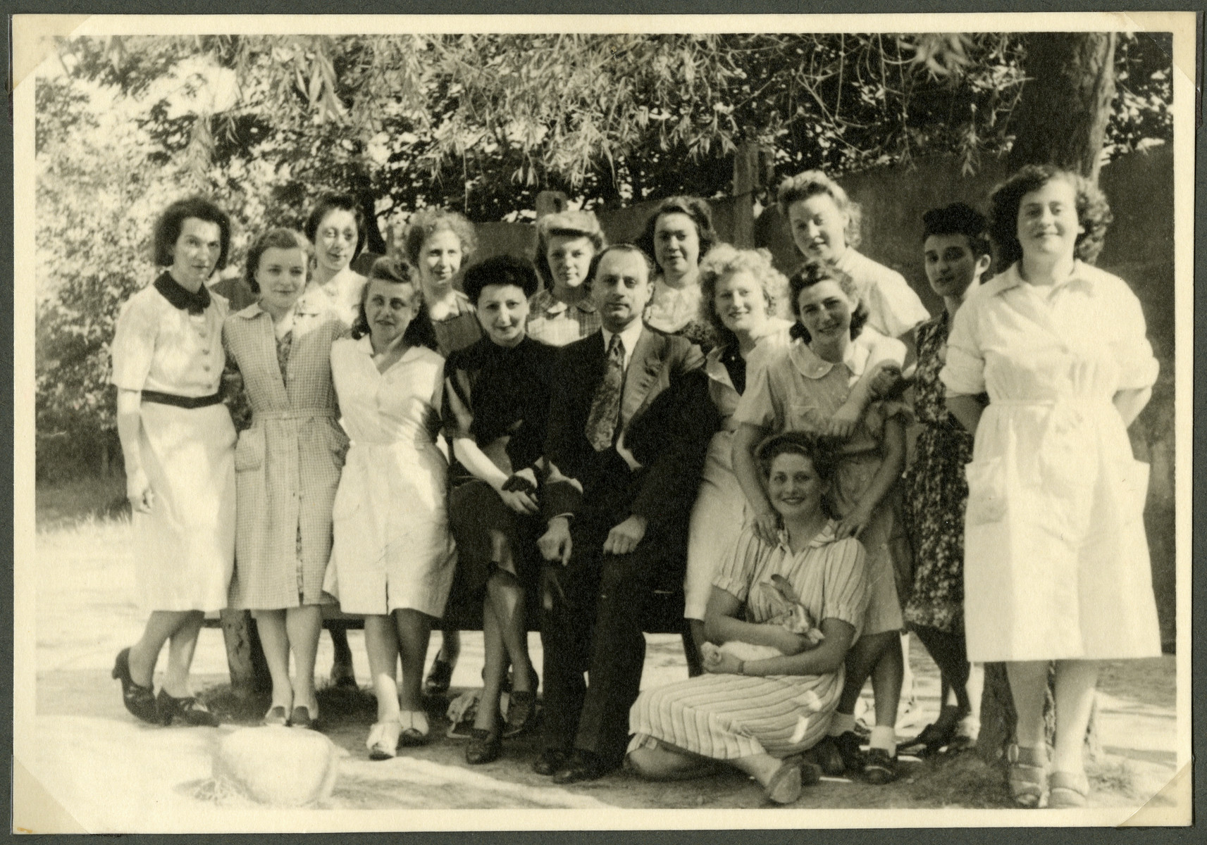 Group portrait of aid workers in what is [possibly the Nos Petits children's home].  Pictured in the center is Fela Perelman.
